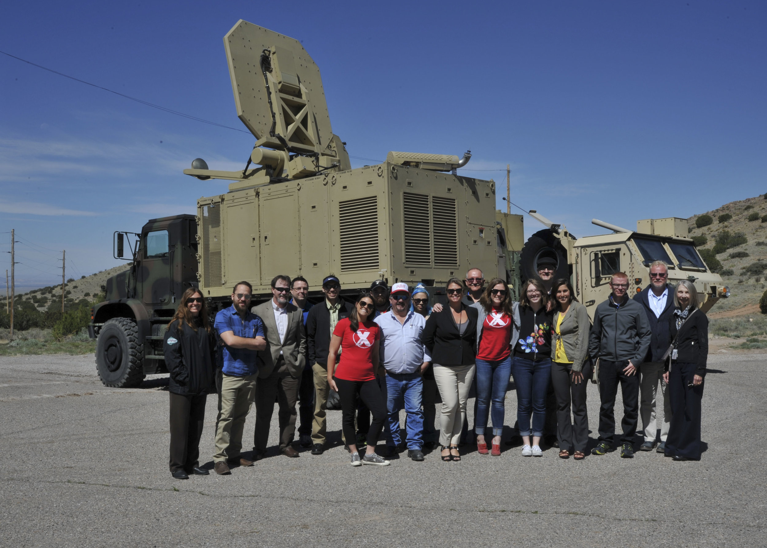 Local community members along with TEDX ABQ members take a photo in front of an active denial truck at Kirtland Air Force Base, New Mexico, May 17. Visitors spent the day learning about high power electromagnetics division technology which is often misrepresented via myth or social media.