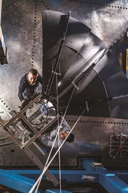 Michael Peterson, top, and Benjamin Urioste test the deployment of a high-strain composite reflector at the Air Force Research Laboratory Space Vehicles Directorate