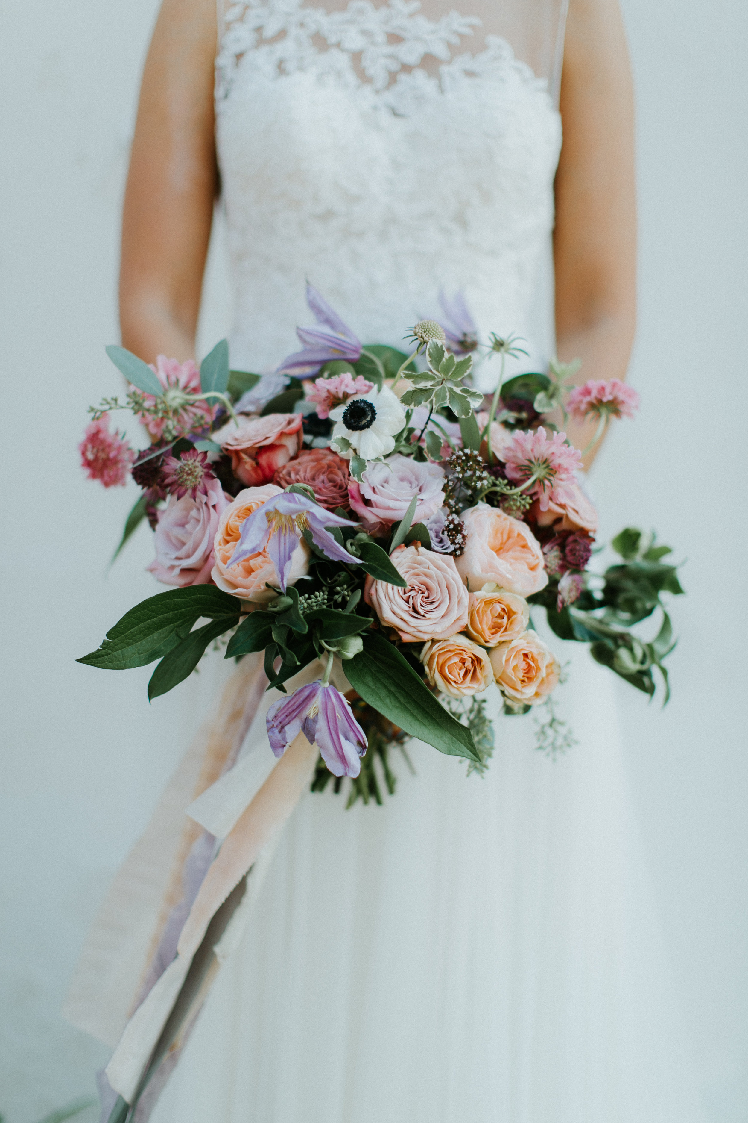 Lush garden style bridal bouquet with clematis, garden rose, anemones, astrantia and scabiosa in shades of lavendar, mauve and peach