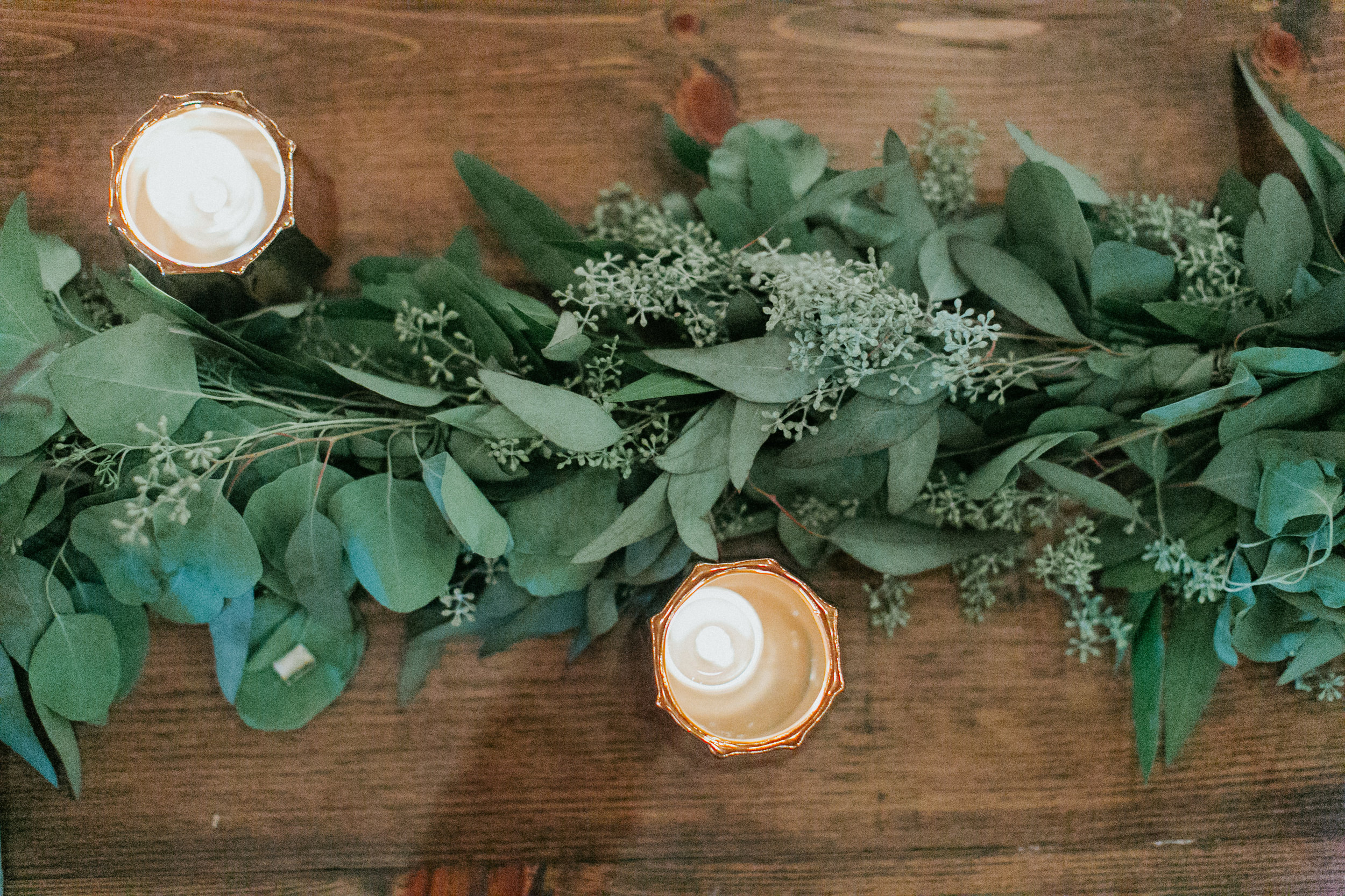Eucalyptus and bay garland on farm tables with copper votives