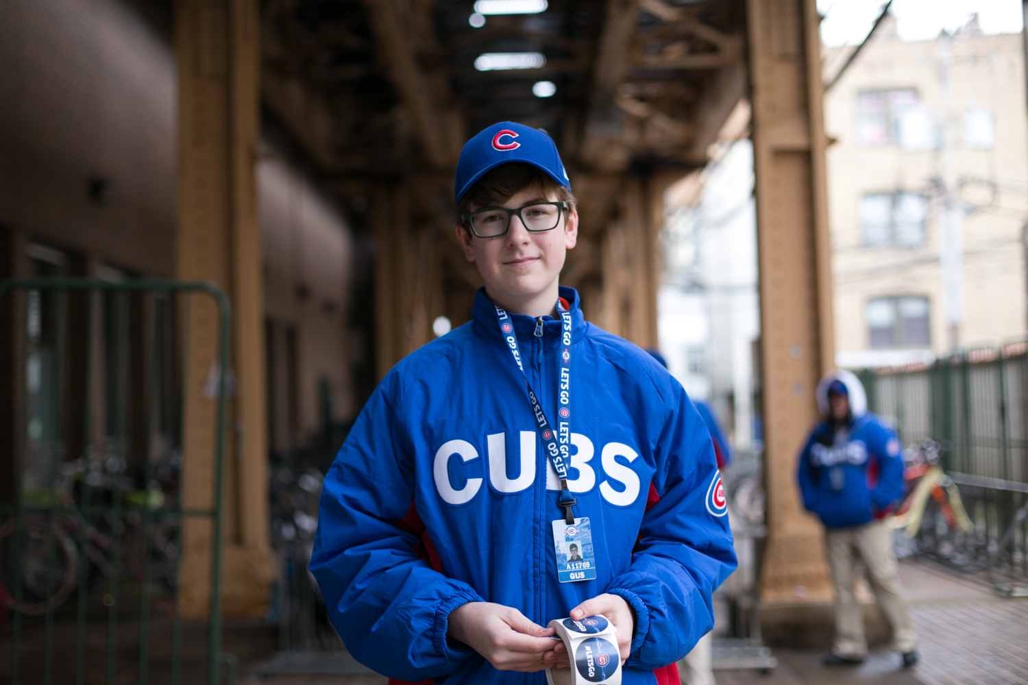 Gus hands out free stickers during his downtime at the bike check outside Wrigley Field. He's happy that his first job is working for his favorite team. 6/24