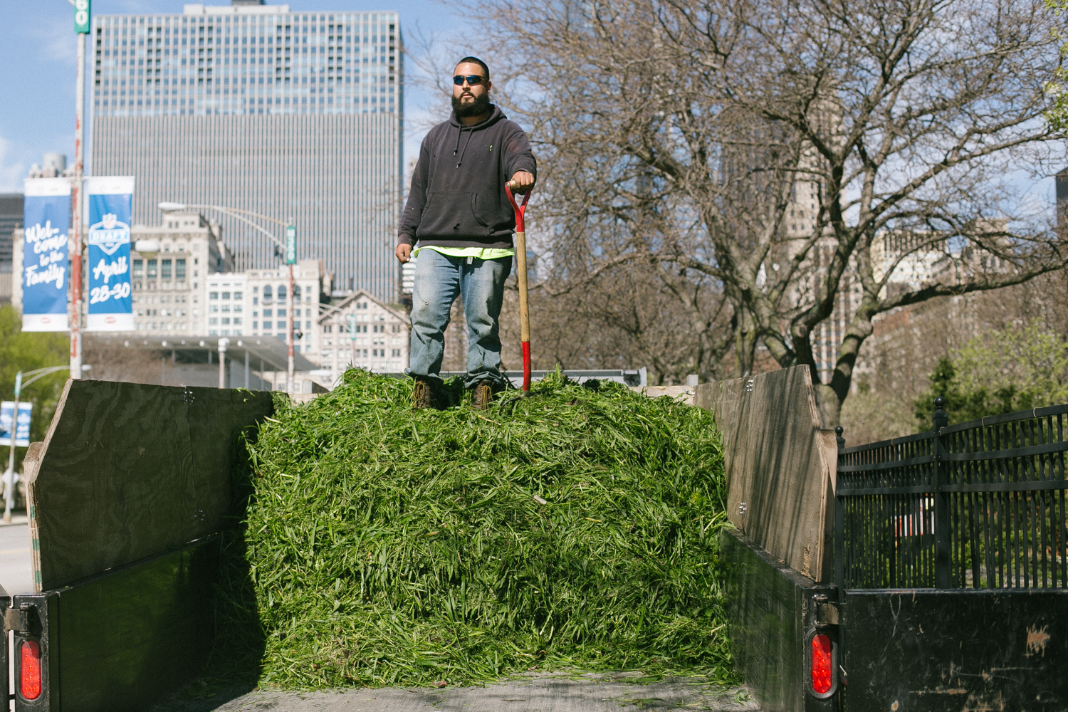 Ramera stands on top of a trailer load of grass clippings after smashing them all down. He has a full day of weed whacking ahead of him. 23/24