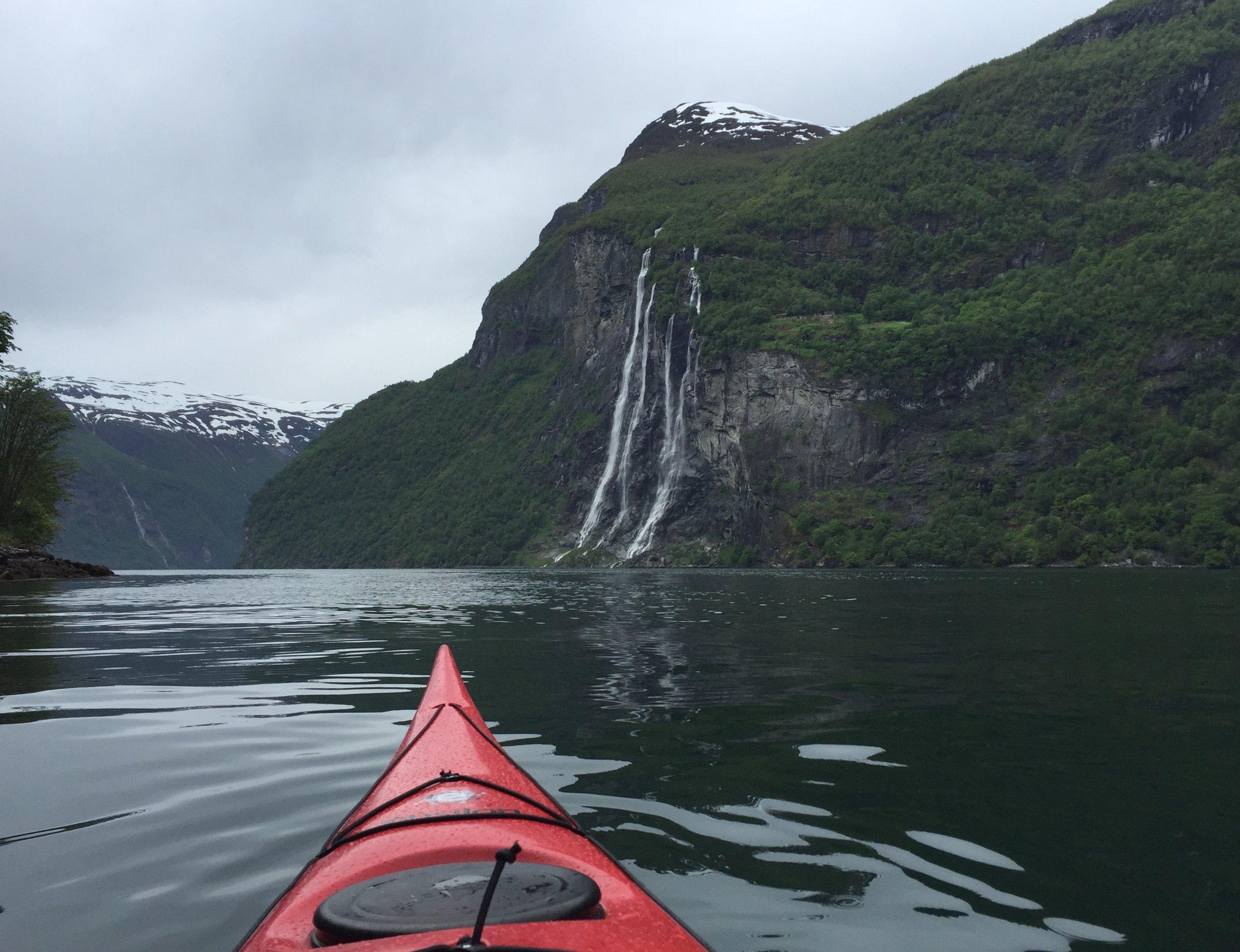 Kayaking in Geirangerfjord, Norway. [View of Seven Sisters Waterfall.]