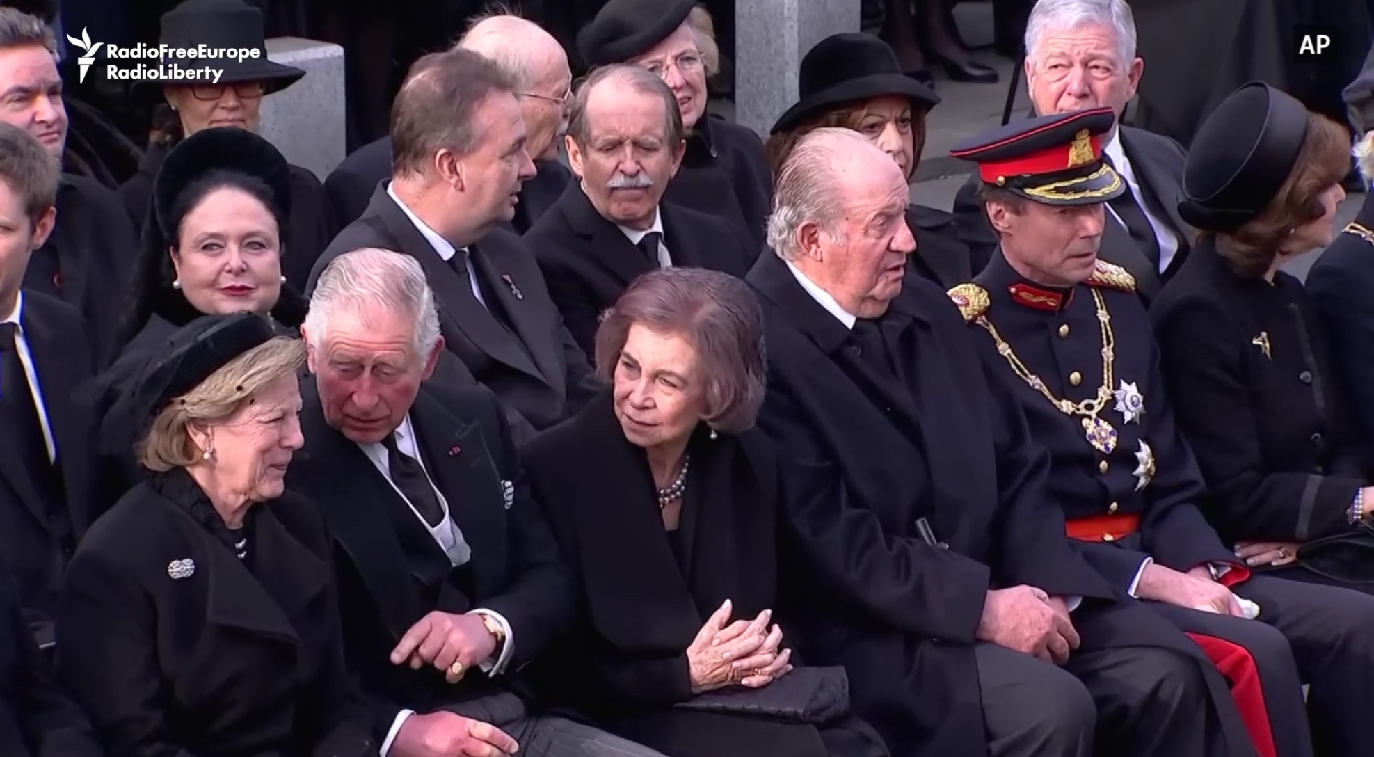 First row, left to right: Queen Anne-Marie of Greece, the Prince of Wales, Queen Sofia of Spain, King Juan Carlos of Spain, Grand Duke Henri of Luxembourg, Queen Silvia of Sweden and (ear showing) King Carl Gustaf of Sweden.  (Reigning royal houses, plus somebody who had once reigned: Queen Anne-Marie of Greece.)  Second row, left to right: The heads of dynasties that no longer reign: the head of the Russian Imperial House (Grand Duchess Maria), the head of the Austrian-Hungarian Imperial House (Archduke Karl), the head of the Portuguese Royal House (Infante Dom Duarte), the Crown Princess of Serbia, and the head of the Serbian Royal House (Crown Prince Alexander of Yugoslavia).