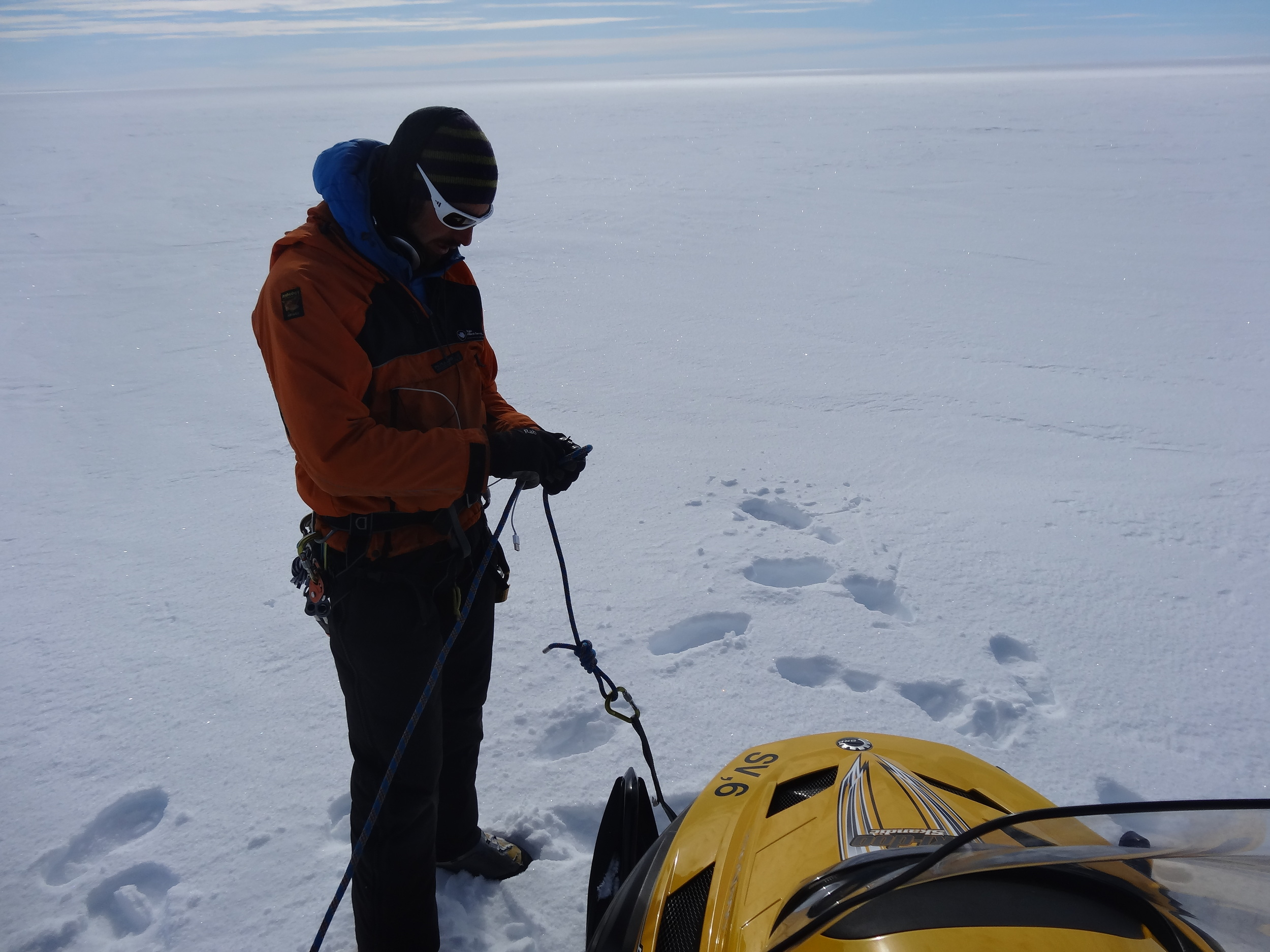 Fixing a rope to investigate some crevasses before driving across with skidoos