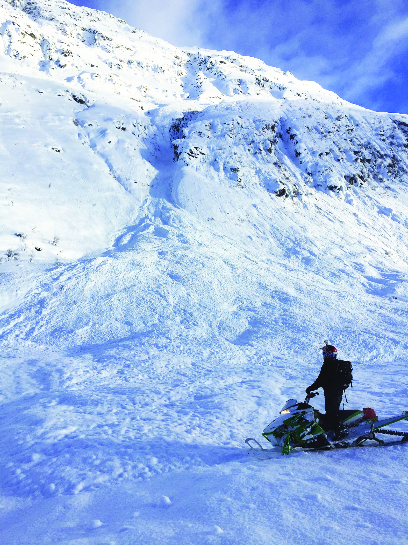 A snowmobile checks out the run out zone from an Avalanche in Hatcher Pass. Photo by S. Carter
