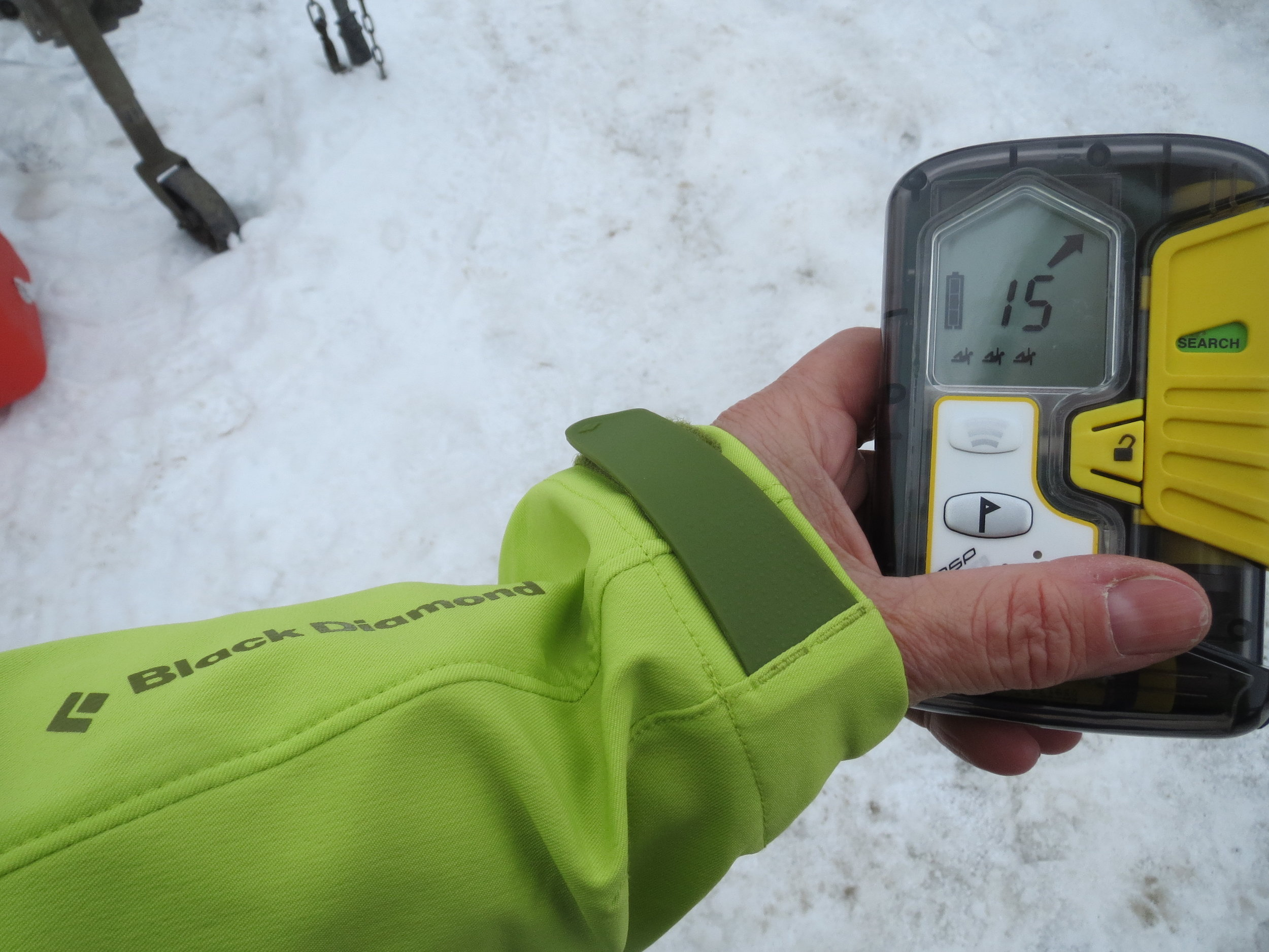 Using an avalanche transceiver to search for a buried victim.