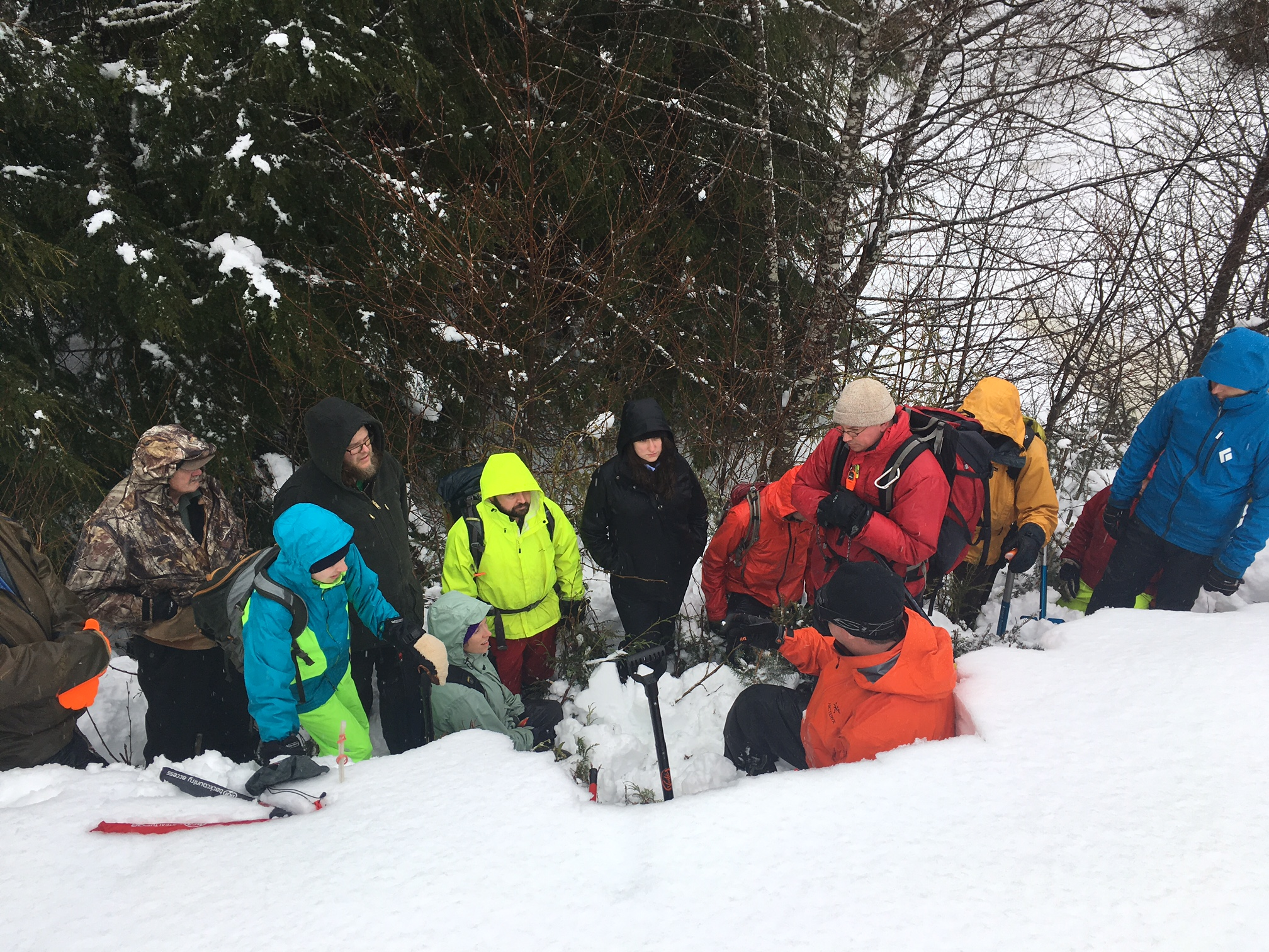 A group of students practice looking at the snow pack. Photo by T. Mattice.