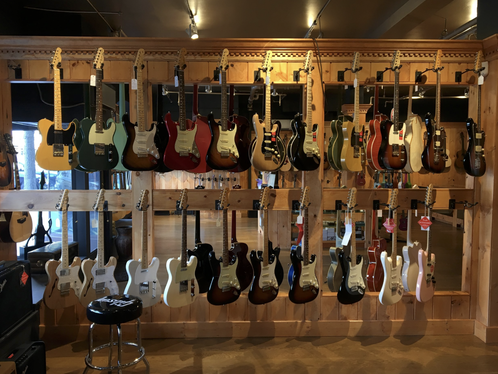 assorted guitars hanging on wall