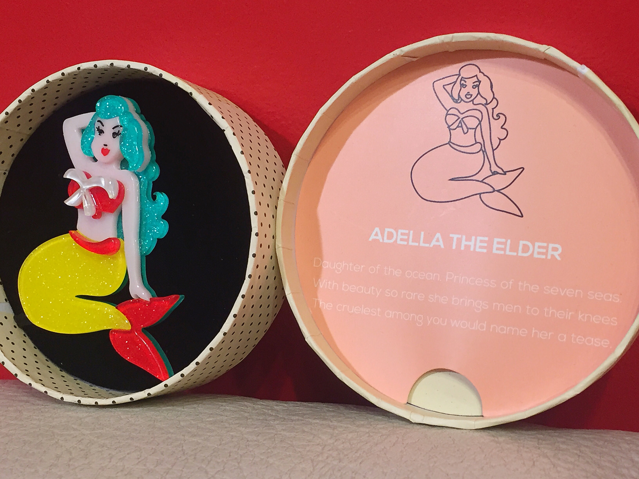 """All Erstwilder pieces come with a backstory. This one reads: """"Adella The Elder: Daughter of the ocean. Princess of the seven seas. With beauty so rare she brings men to their knees. The cruelest among you would name her a tease."""" Adella the Elder pin, $38"""