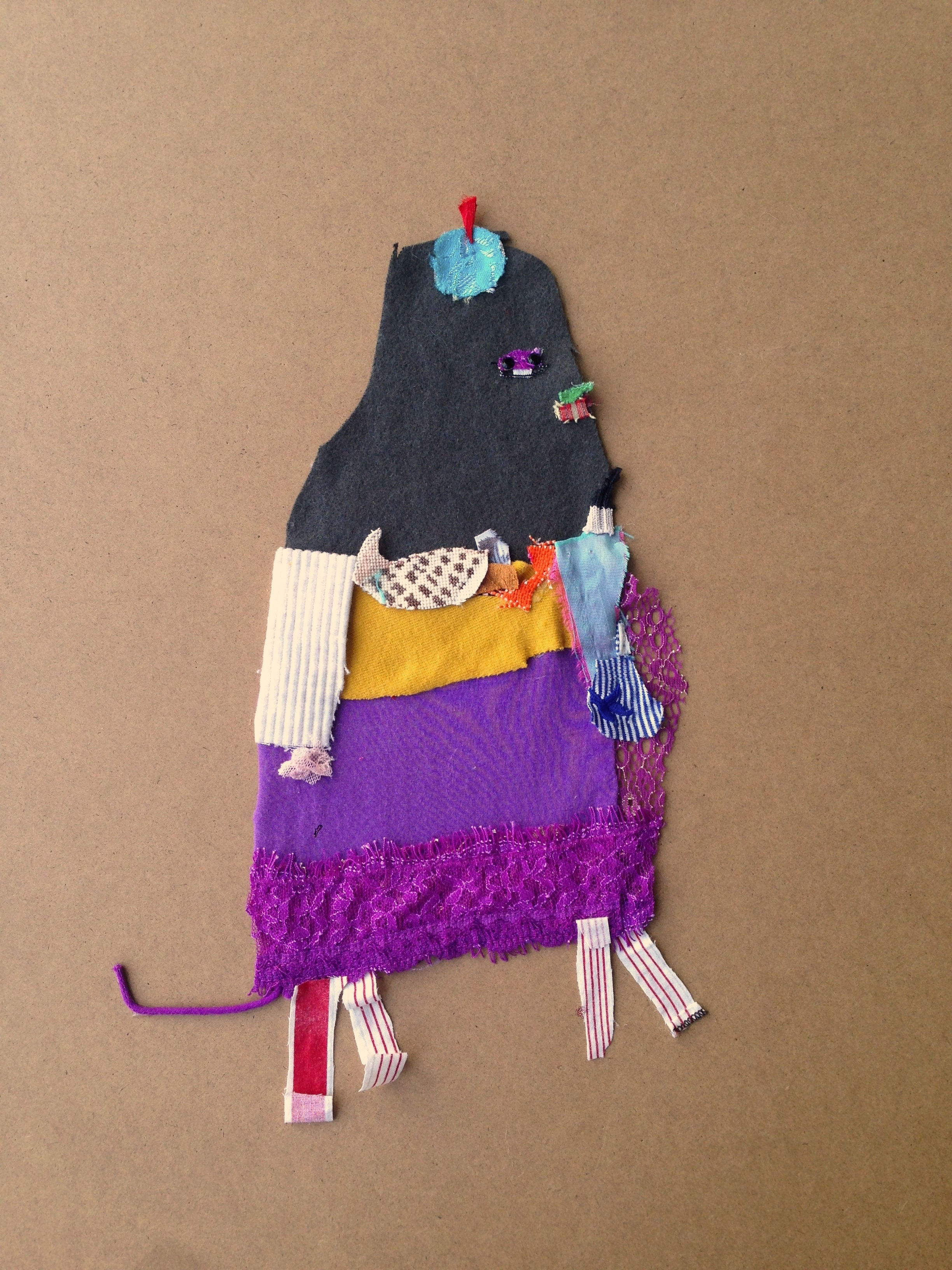Walrus in a Nanna Suit  20.5 x 20.5 inches  Recycled fabric: Chinese jewelry bag, piece of a doll made with Oma, silk curtains, shark pajamas, old silk napkin, purple lace slinky shirt, hand me down  corduroy skirt, an heirloom cross-stitched shell on a tea towel and the trim of a summer dress.  2015