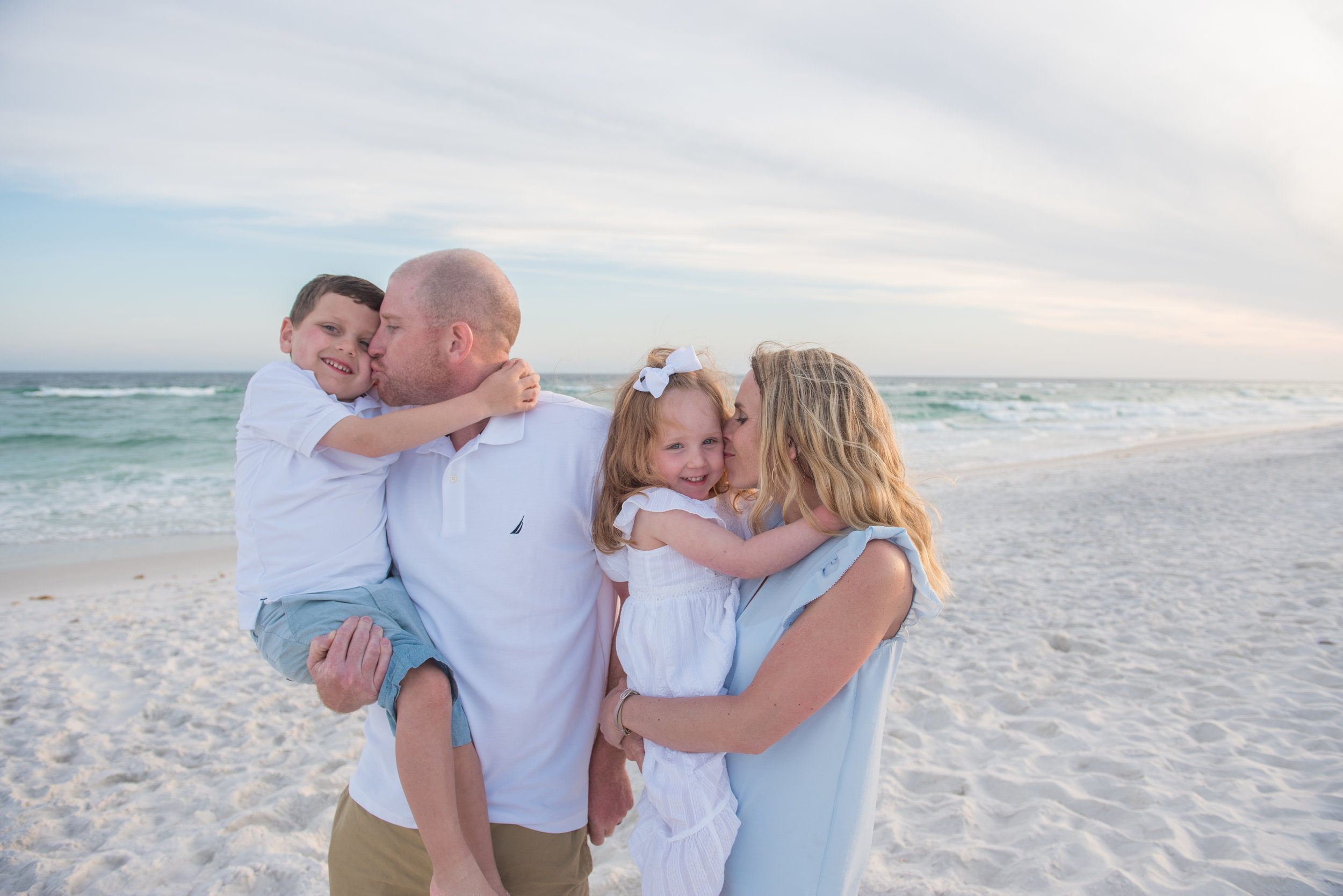 mom and dad holding kids by beach- Pensacola vacation family Photographer