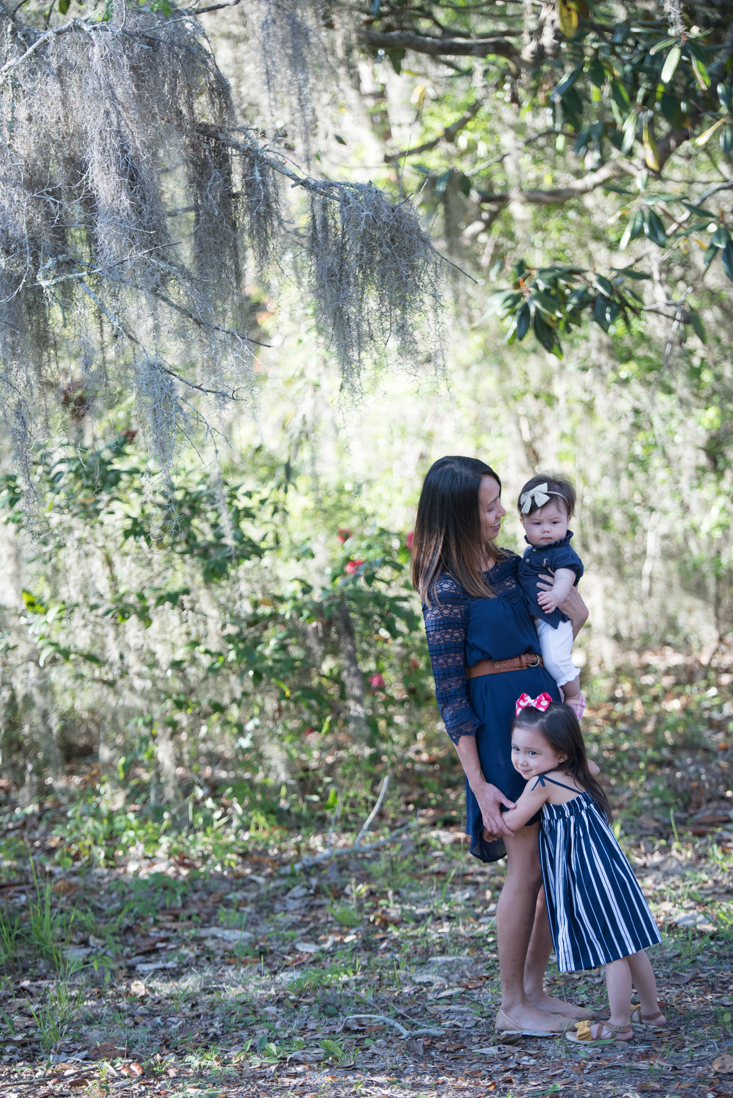 mom with two girls by moss- Navarre Family Photographer