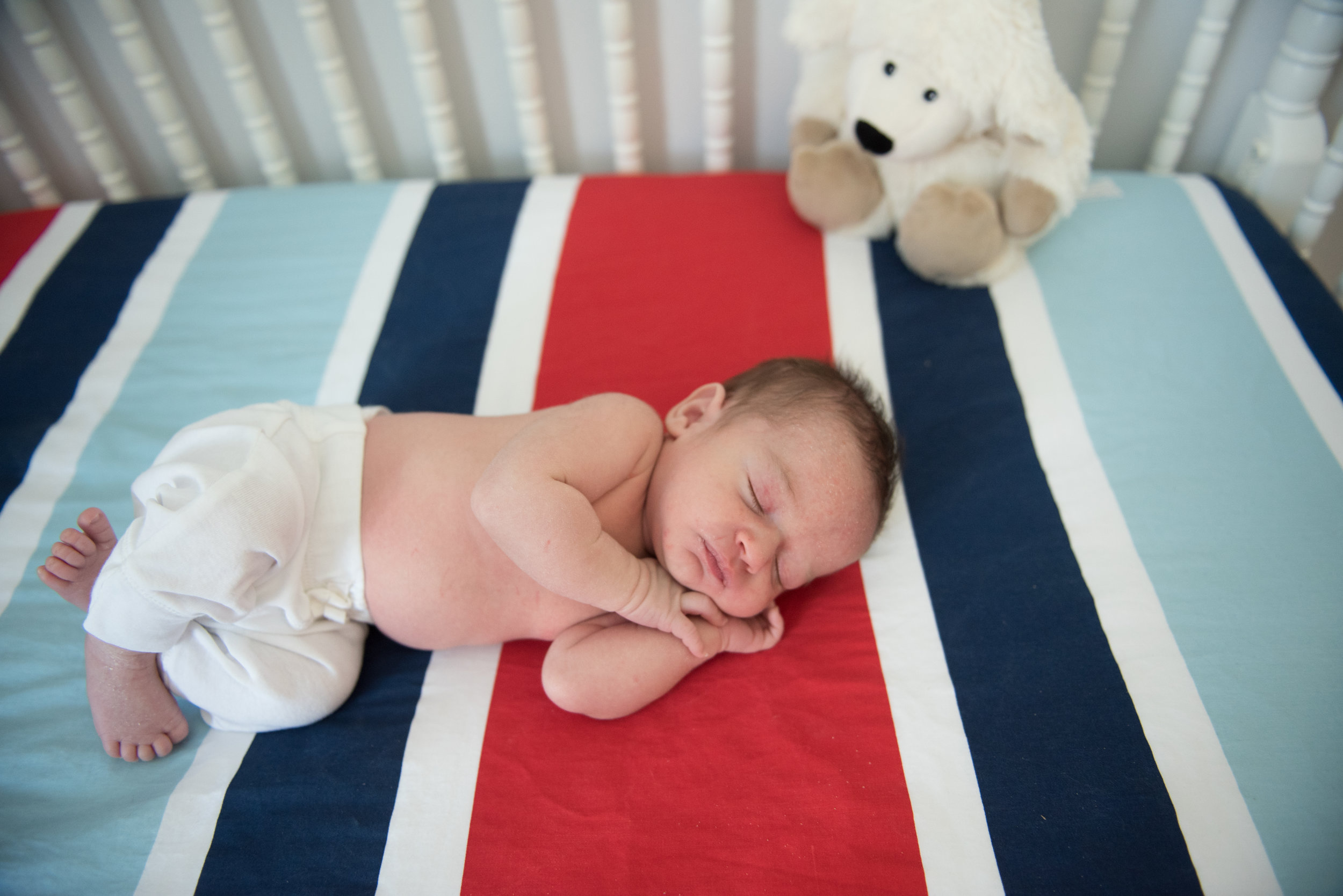 baby in cribs with stripes-Pensacola Newborn Photographer