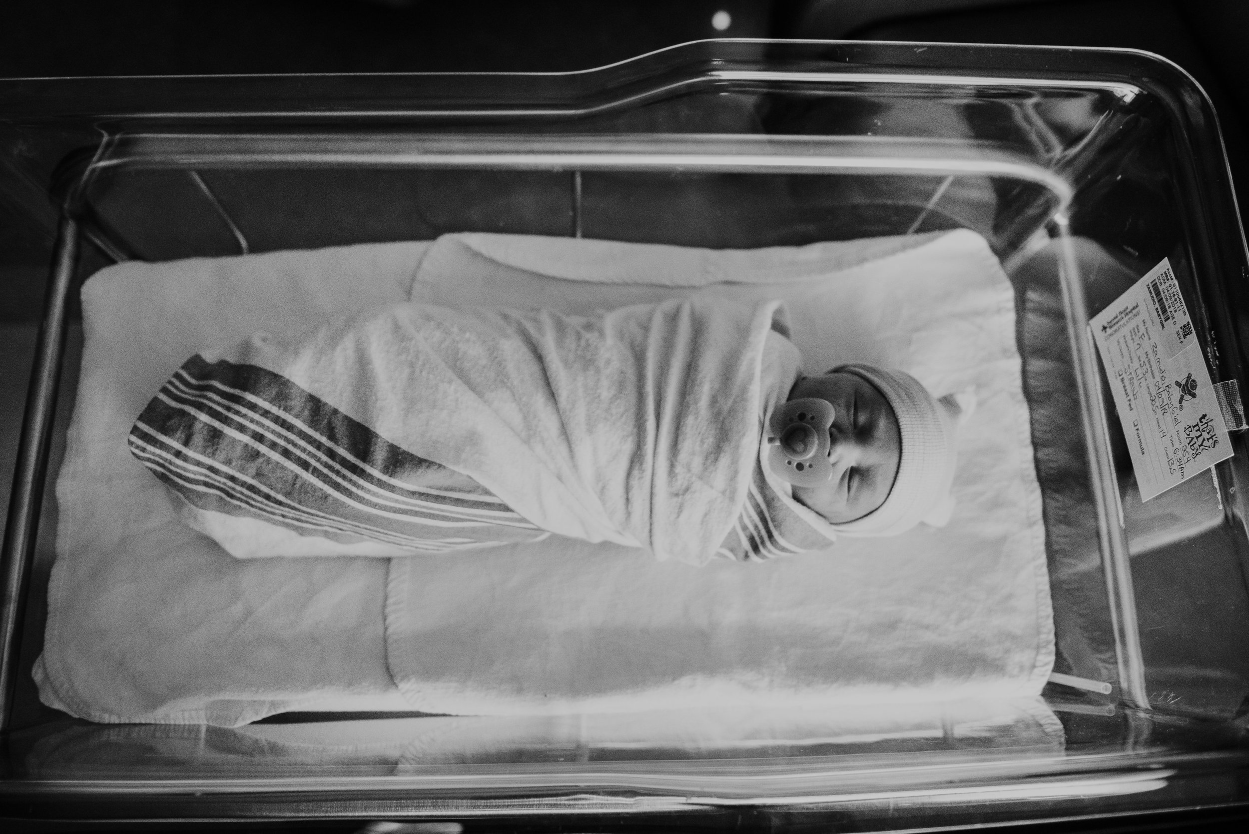 black and white of child in crib-pensacola child photographer