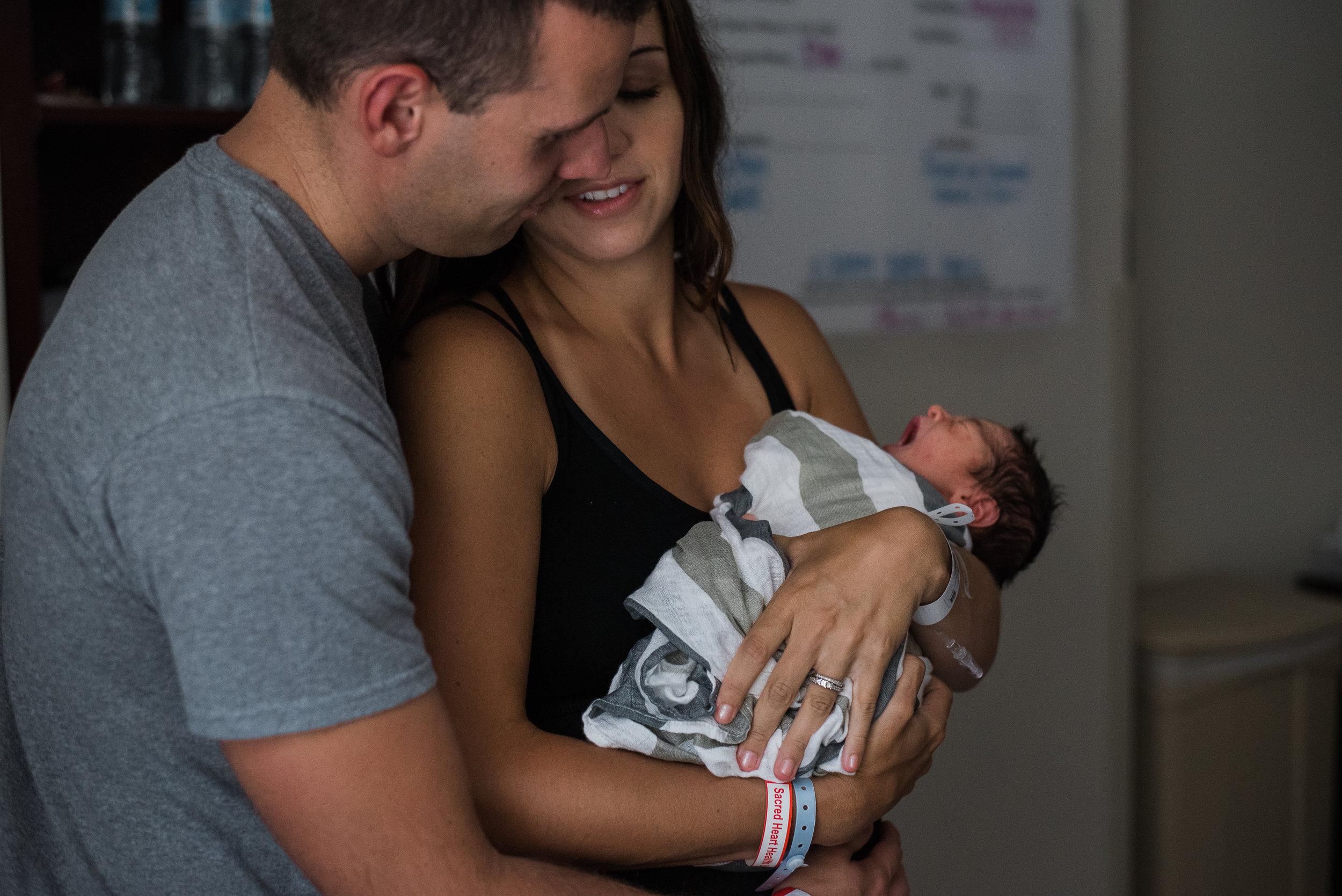 mom and dad holding baby-Pensacola Newborn Photographer