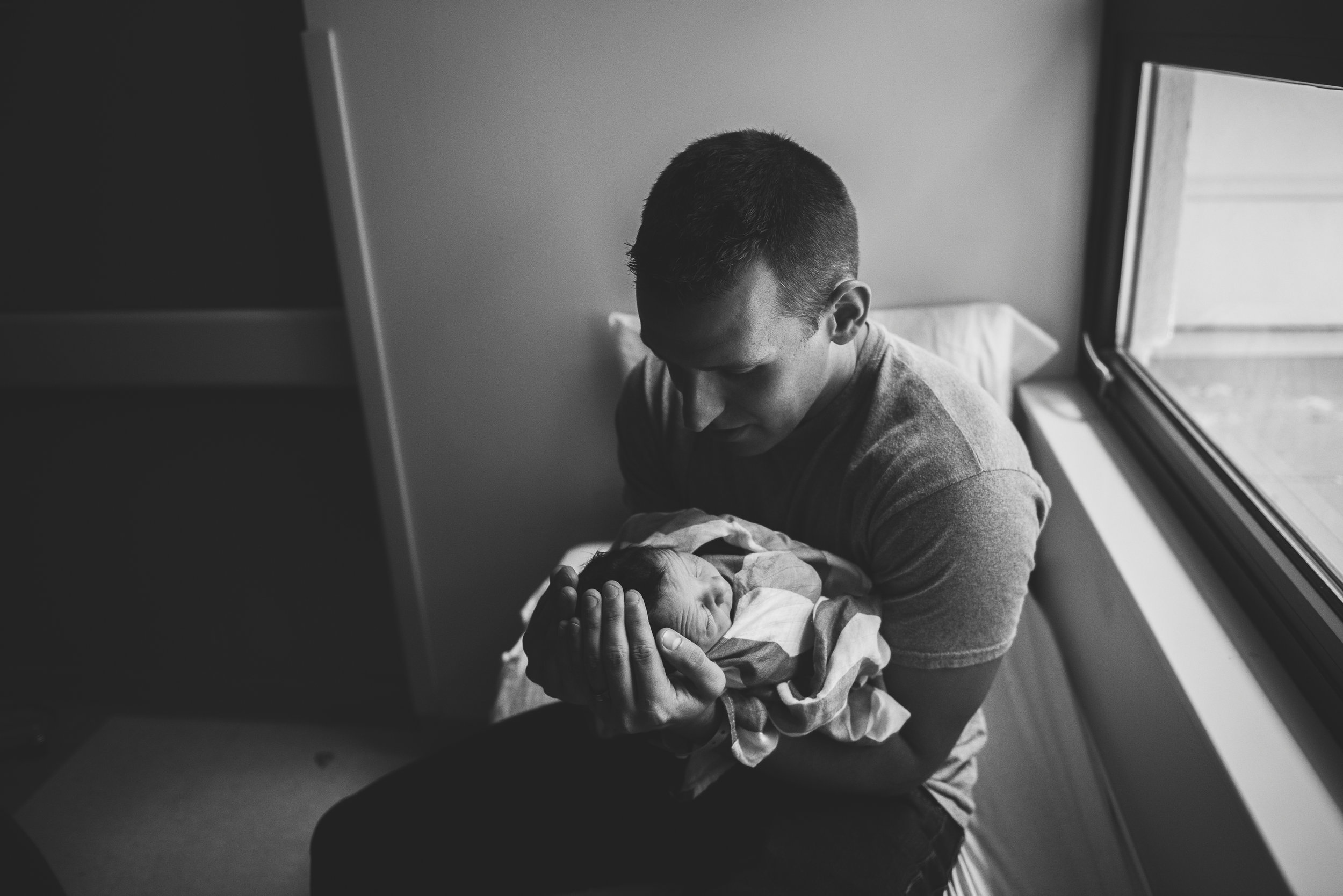 dad holding baby in arms- Pensacola Newborn Photographer