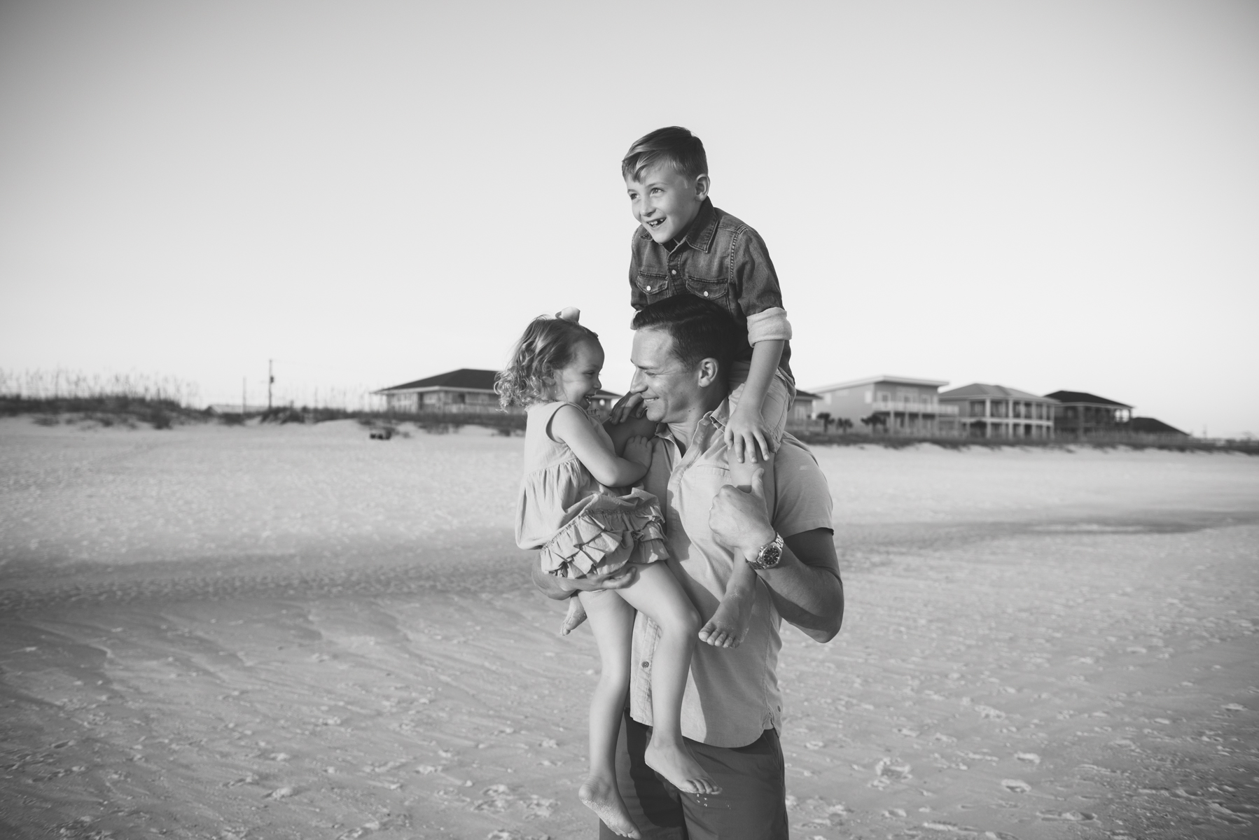 kids on dads shoulder at beach-pensacola beach family photographer