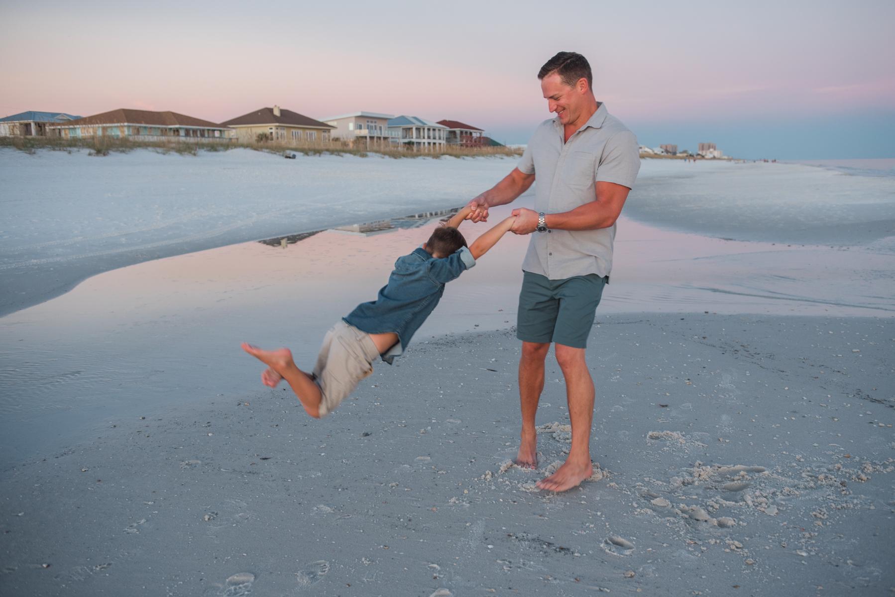 dad swinging son at beach-pensacola family photographer