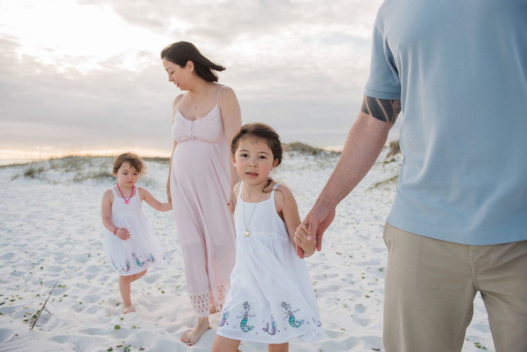 family holding hands at beach