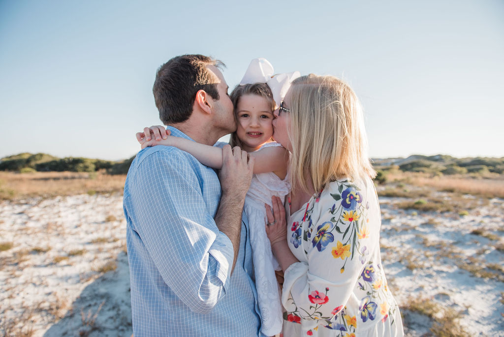 mom and dad kissing girl at beach-pensacola beach family photographer