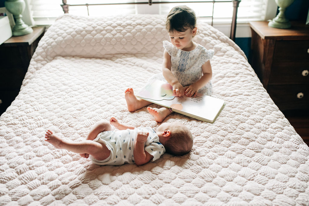 sister reading to baby-pensacola newborn photographer
