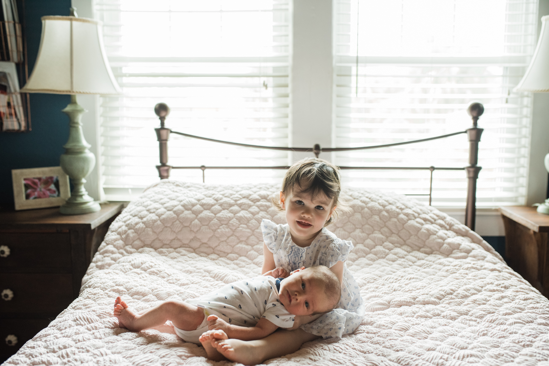 baby holding sister on bed-pensacola newborn photographer