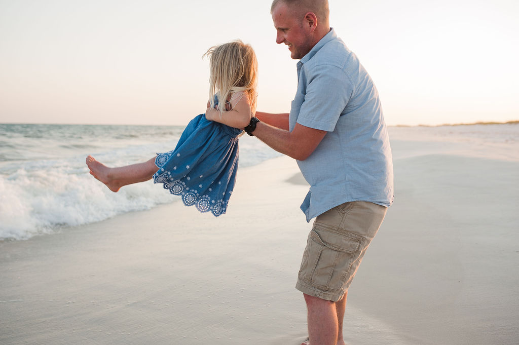 dad swinging daughter in waves- Navarre Beach Family Photographer