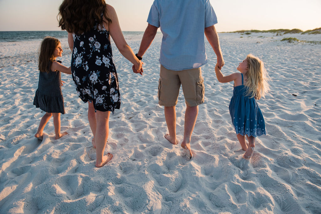 family walking on beach-pensacola beach family photographer