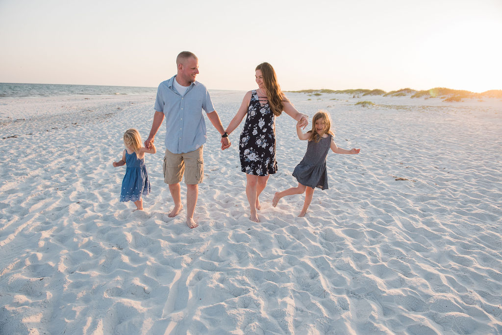 family holding hands by beach-pensacola beach photographer