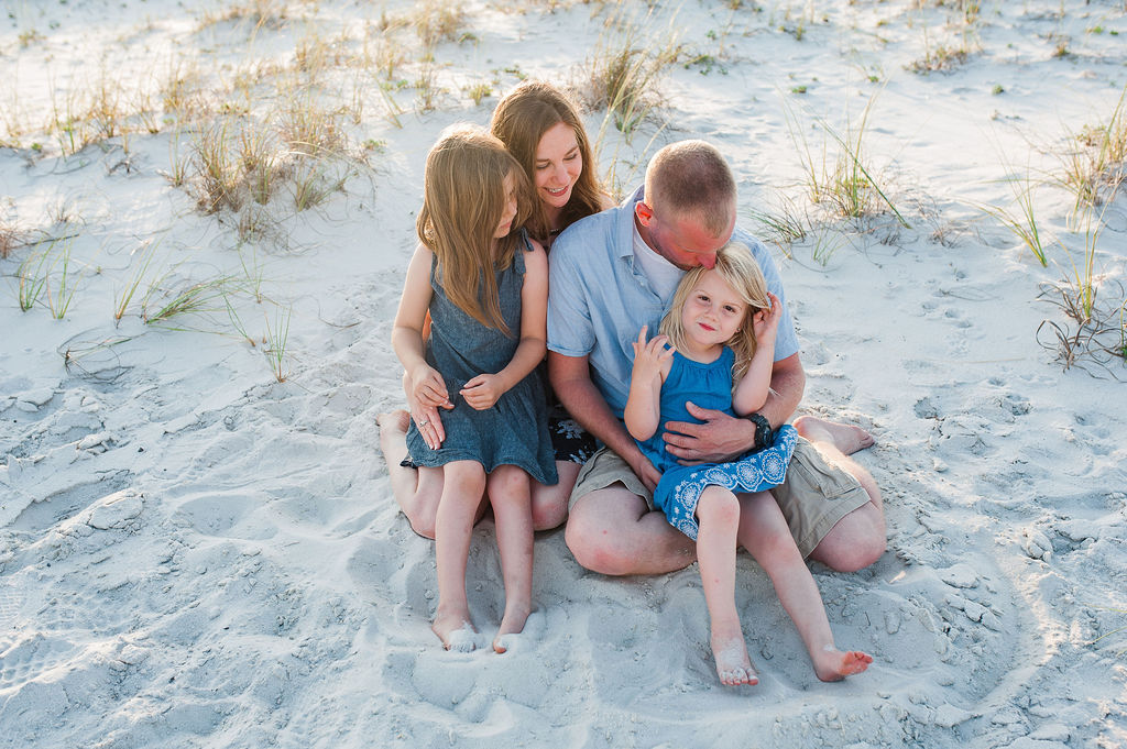 family embracing on sand dunes by beach