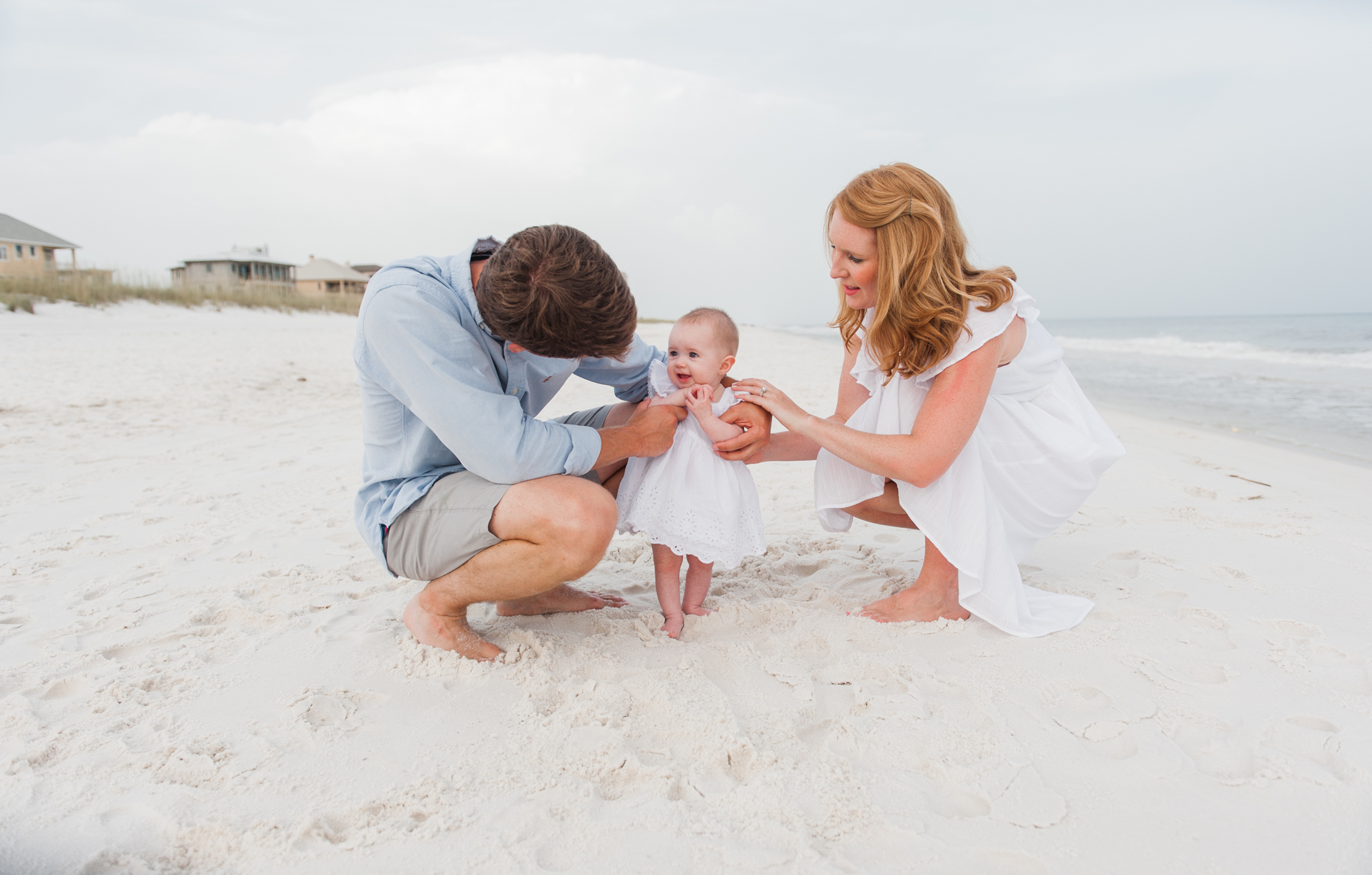 mom and dad with baby in sand-pensacola beach family photographer