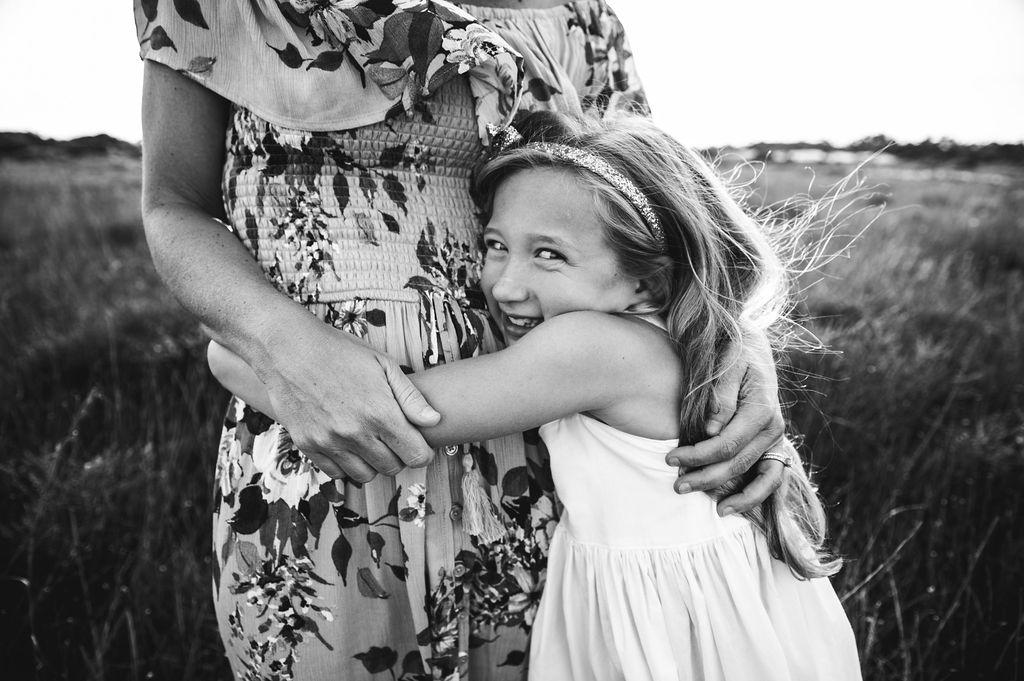 girl hugging mom in seagrass-pensacola beach family photographer