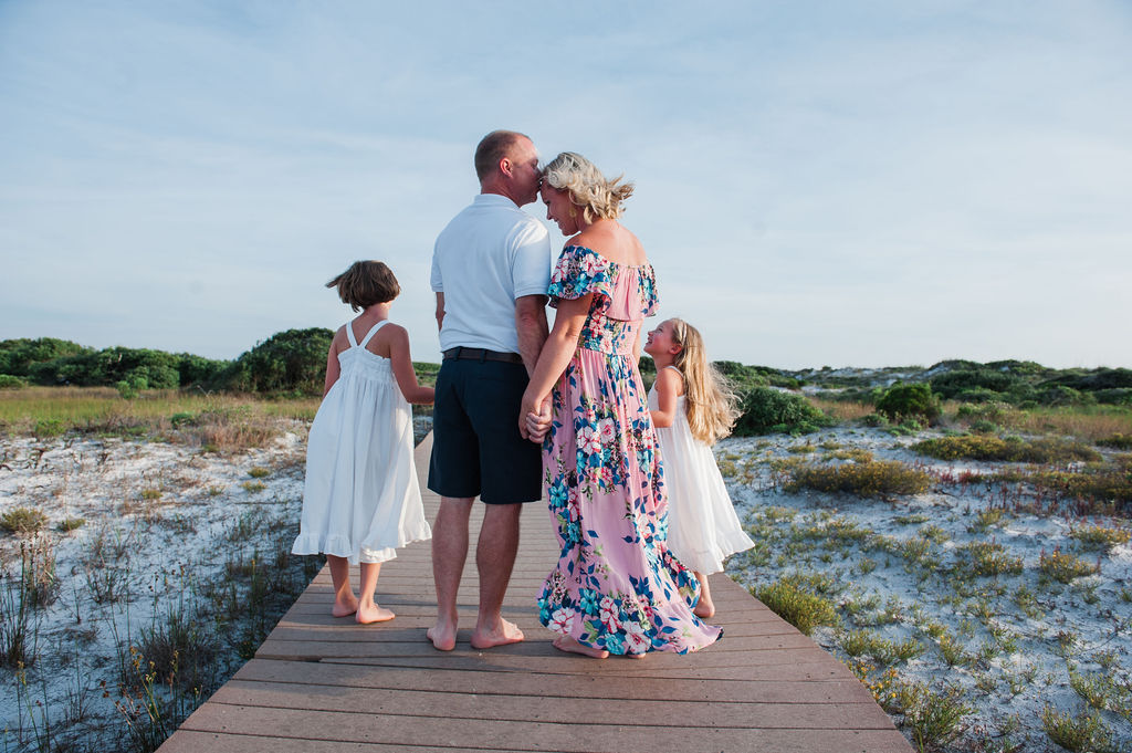 dad giving mom kisses on boardwalk-pensacola family photographer