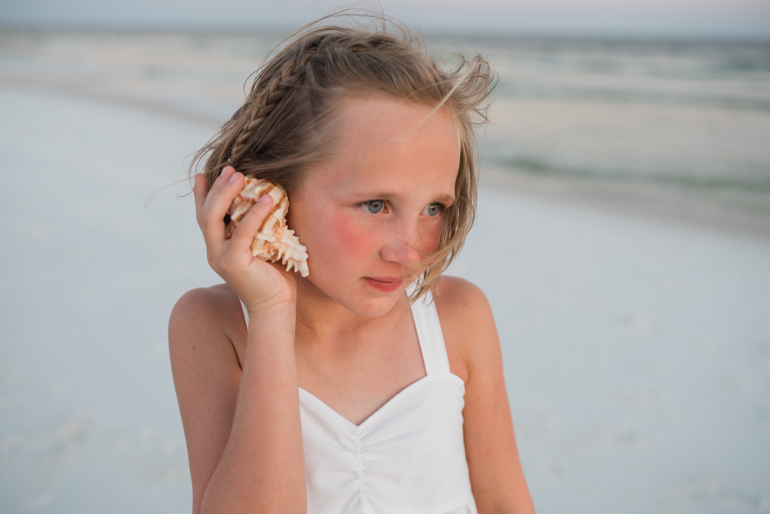 girl holding shell to ear-pensacola family photographer