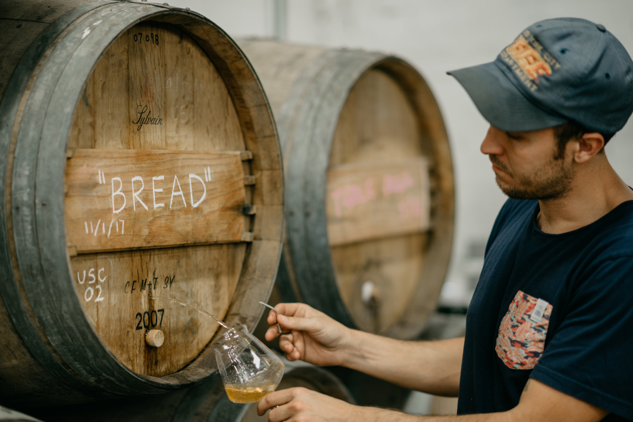 Photo of Mike taking a sample of Bread from one of our barrels