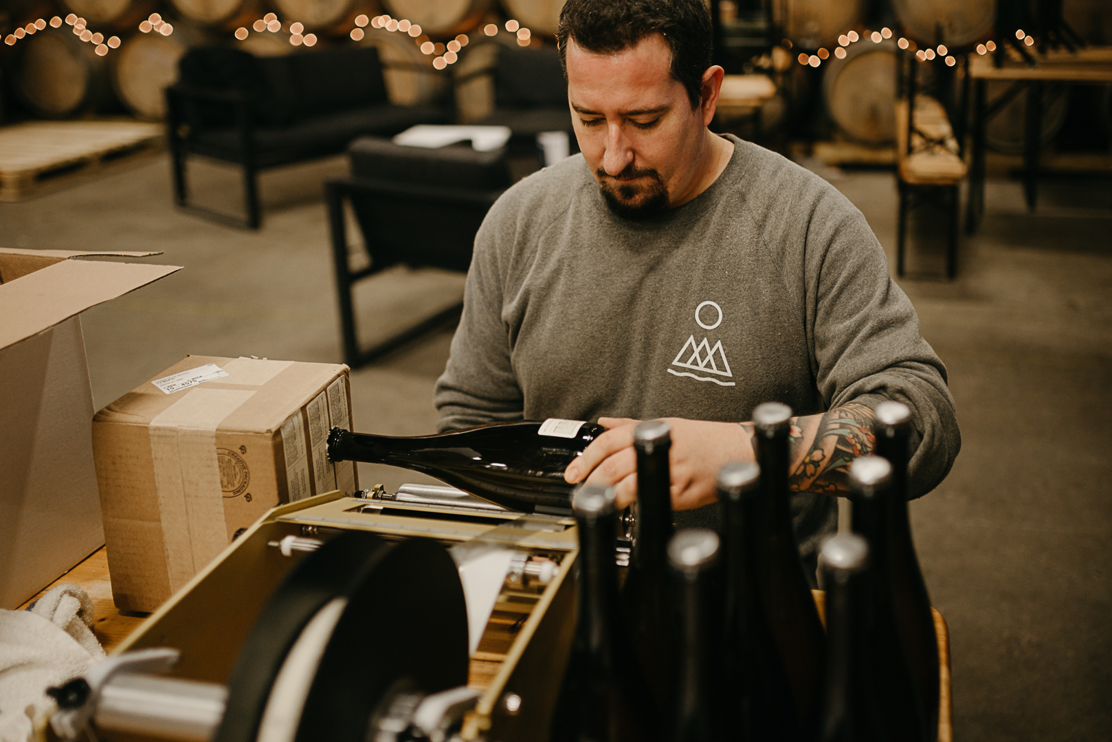 Photo of Josh labeling the most recent bottles of Valley Beer