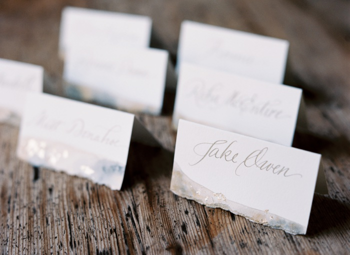 We hand painted all the place cards, to mimic the invitation, then tore the edge for texture.