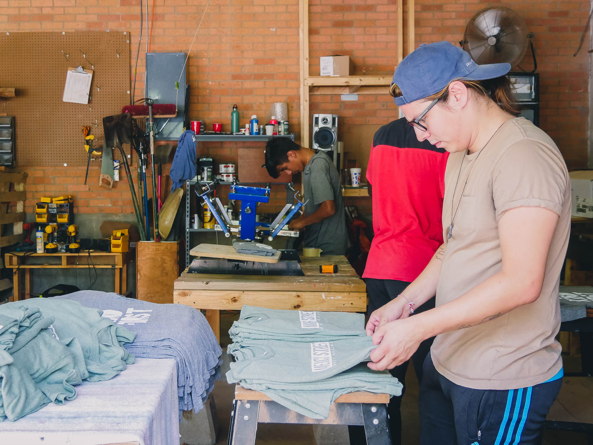 Oscar working in the t-shirt press during the summer Leadership Intensive.