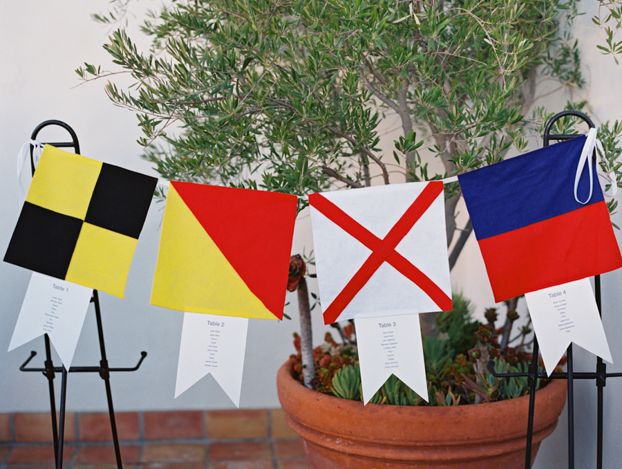 The groom at this wedding had a career in the navy. So of course when we got to the seating chart we had to go with a navy theme. The flags each represent an international maritime letter and they spell out L-O-V-E. Who says nautical can't be romantic?  Photo by:  Lavender & Twine   Venue:  Ojai Valley Inn & Spa