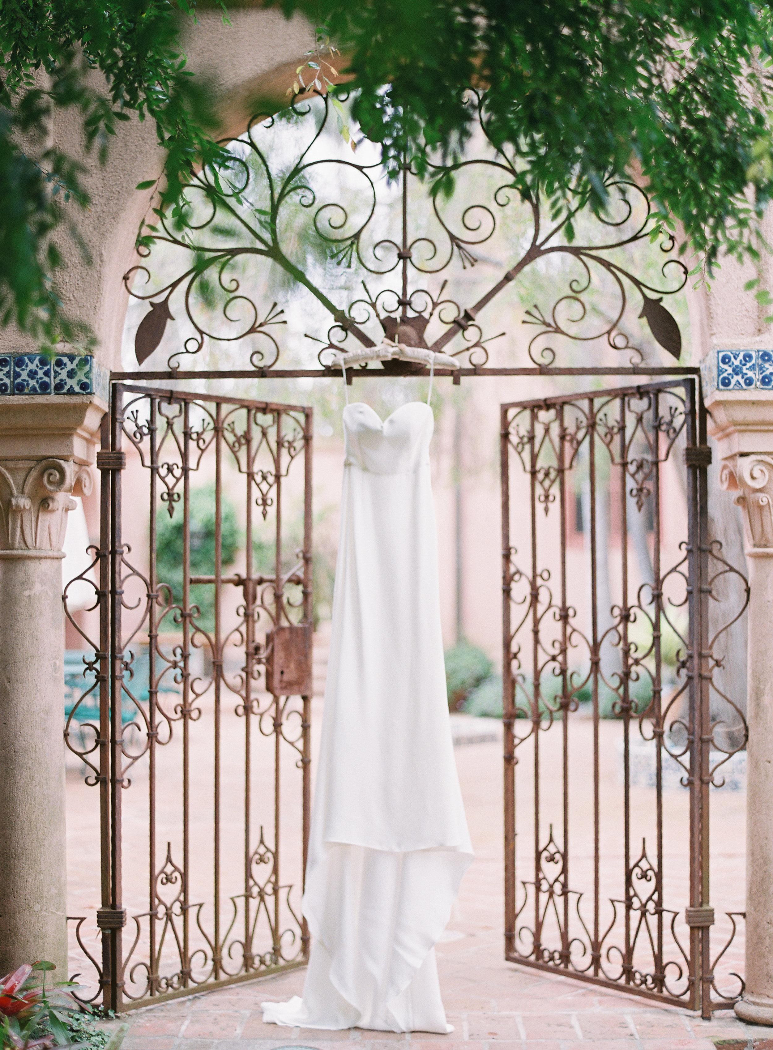 simple silk wedding dress on vintage iron gate