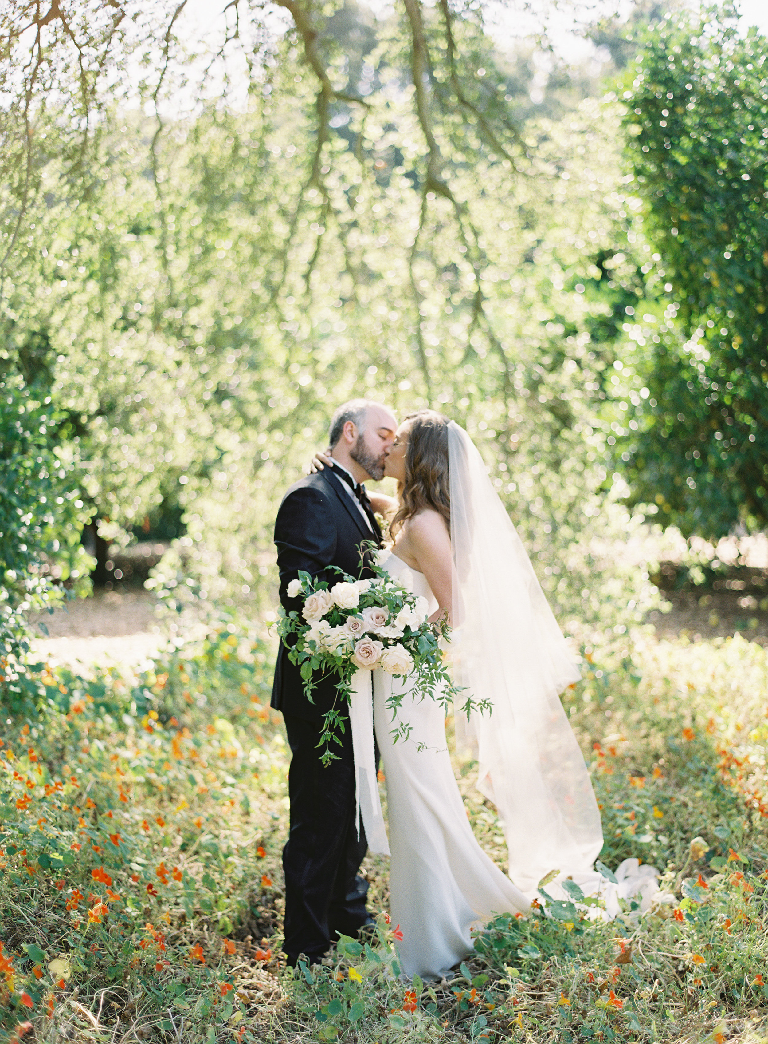 bride and groom kiss amongst the flowers