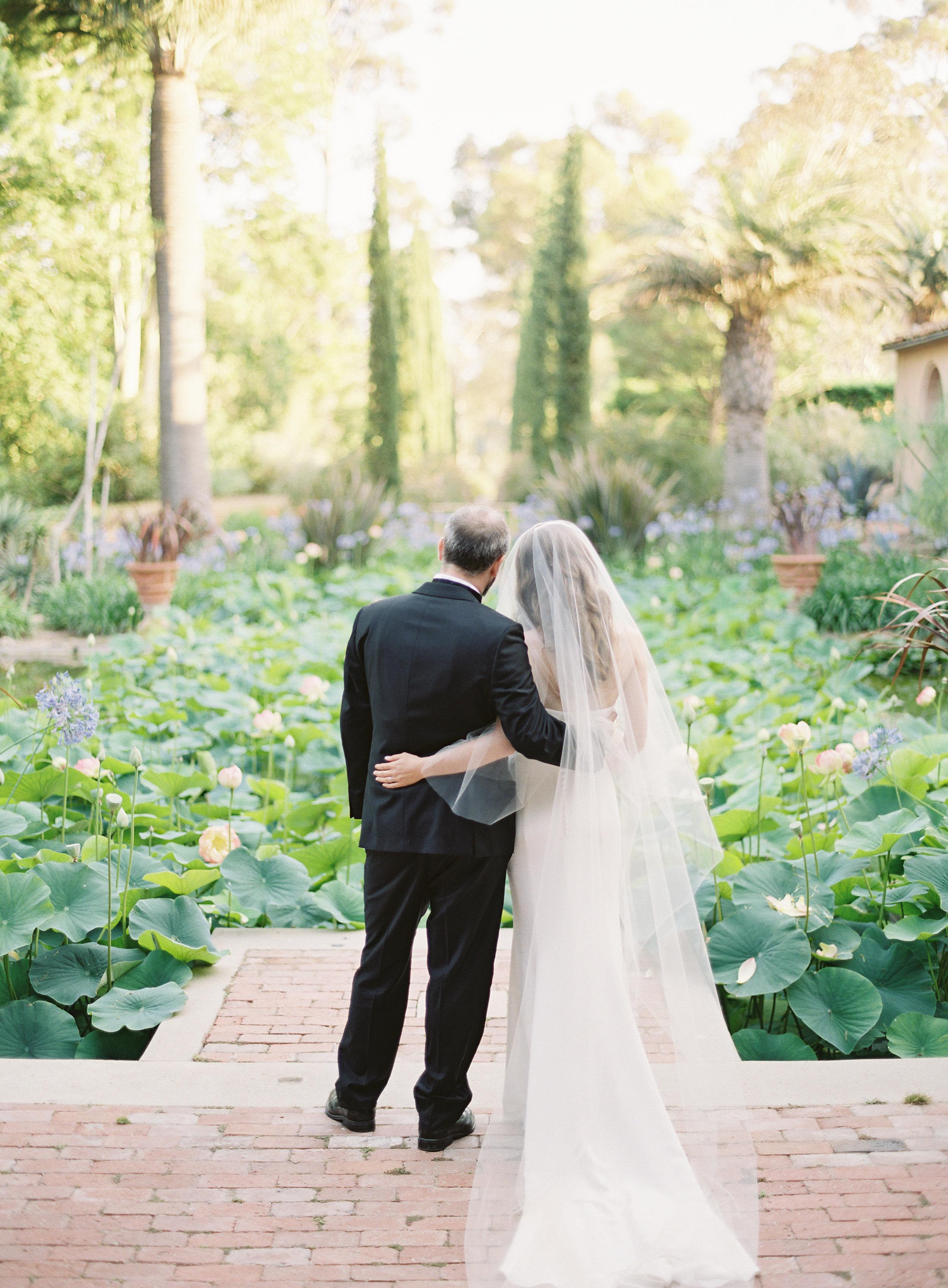 bride and groom overlooking lotus pond