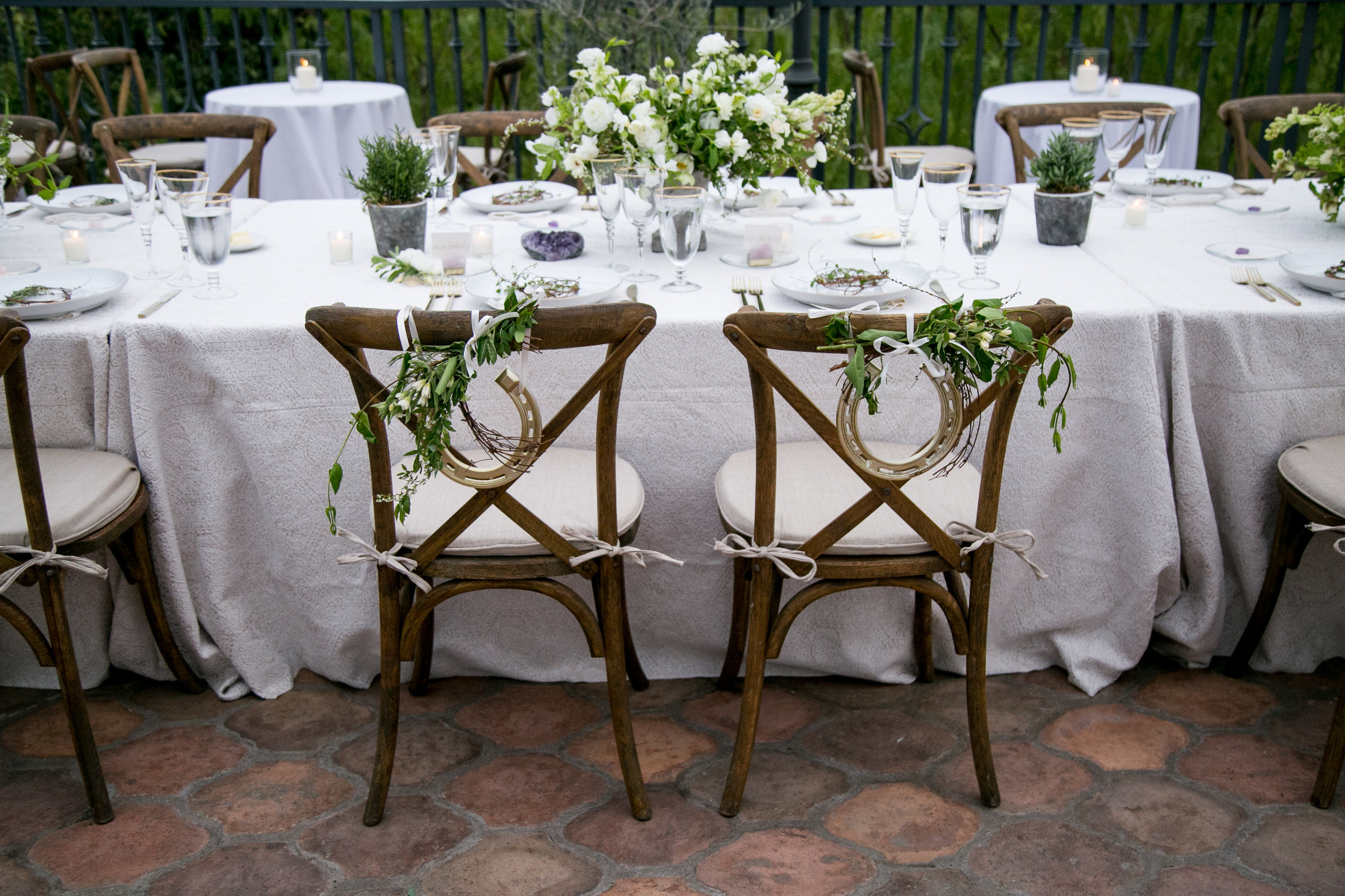 bride and groom chairs adorned with greenery