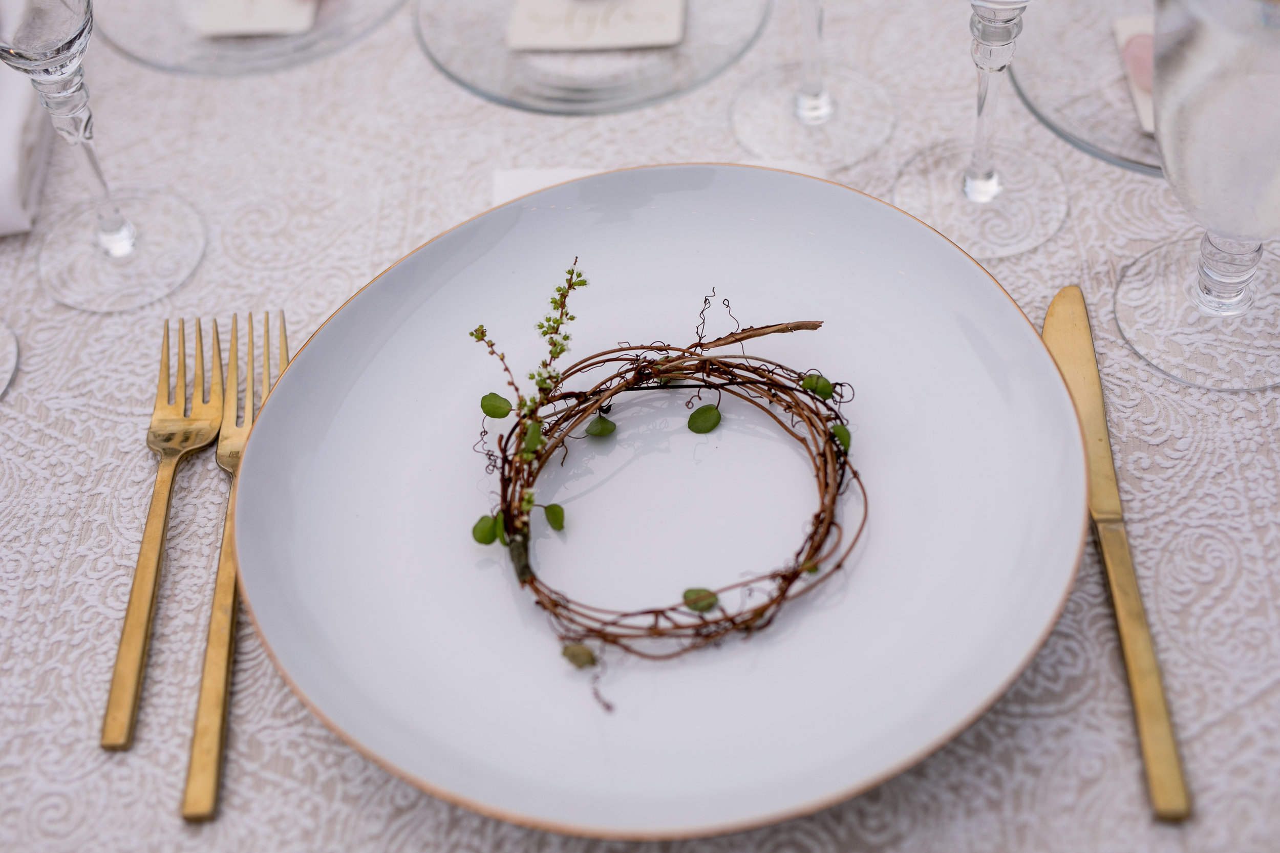 table setting with natural elements and gold flatware