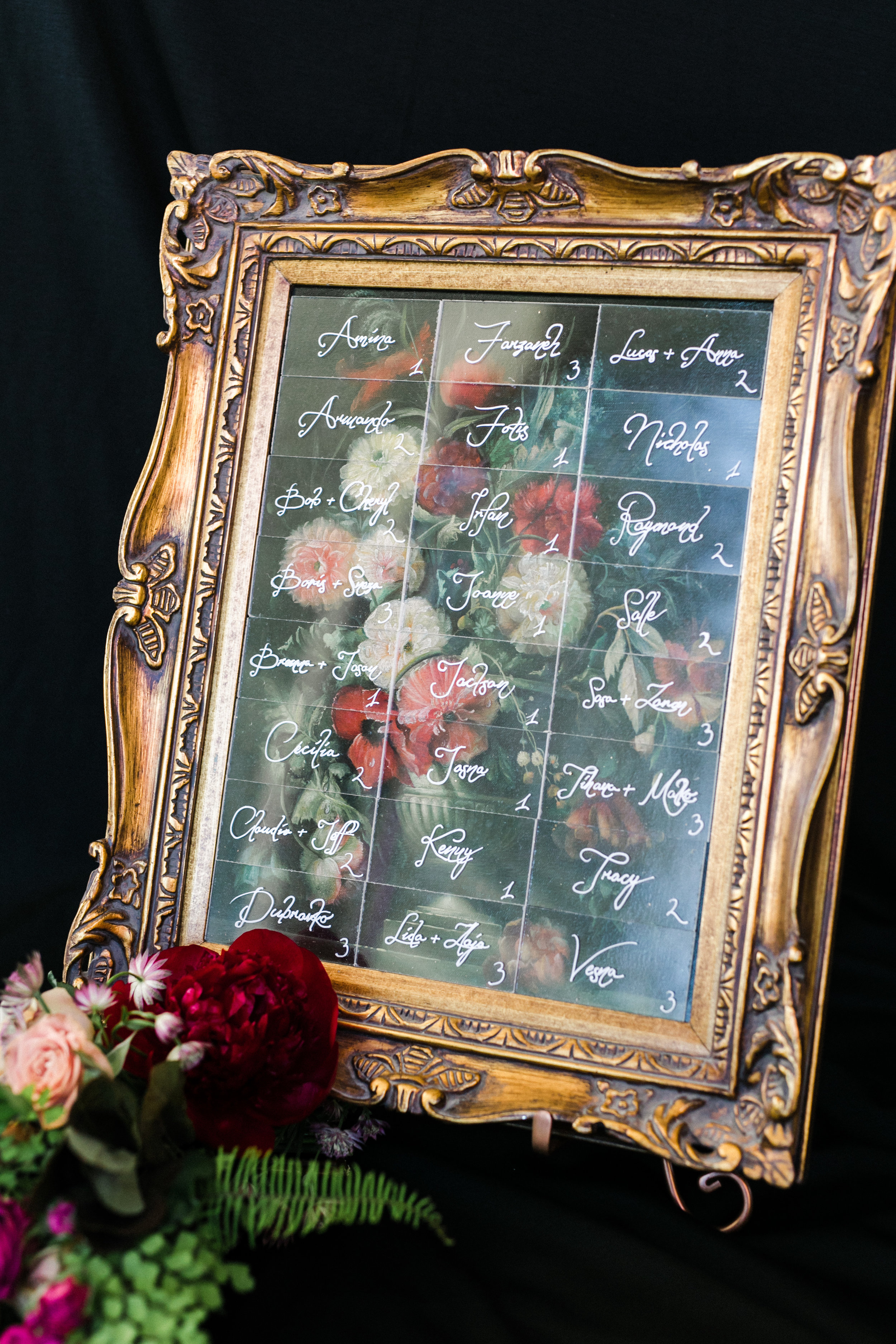 calligraphed seating chart in vintage gold frame