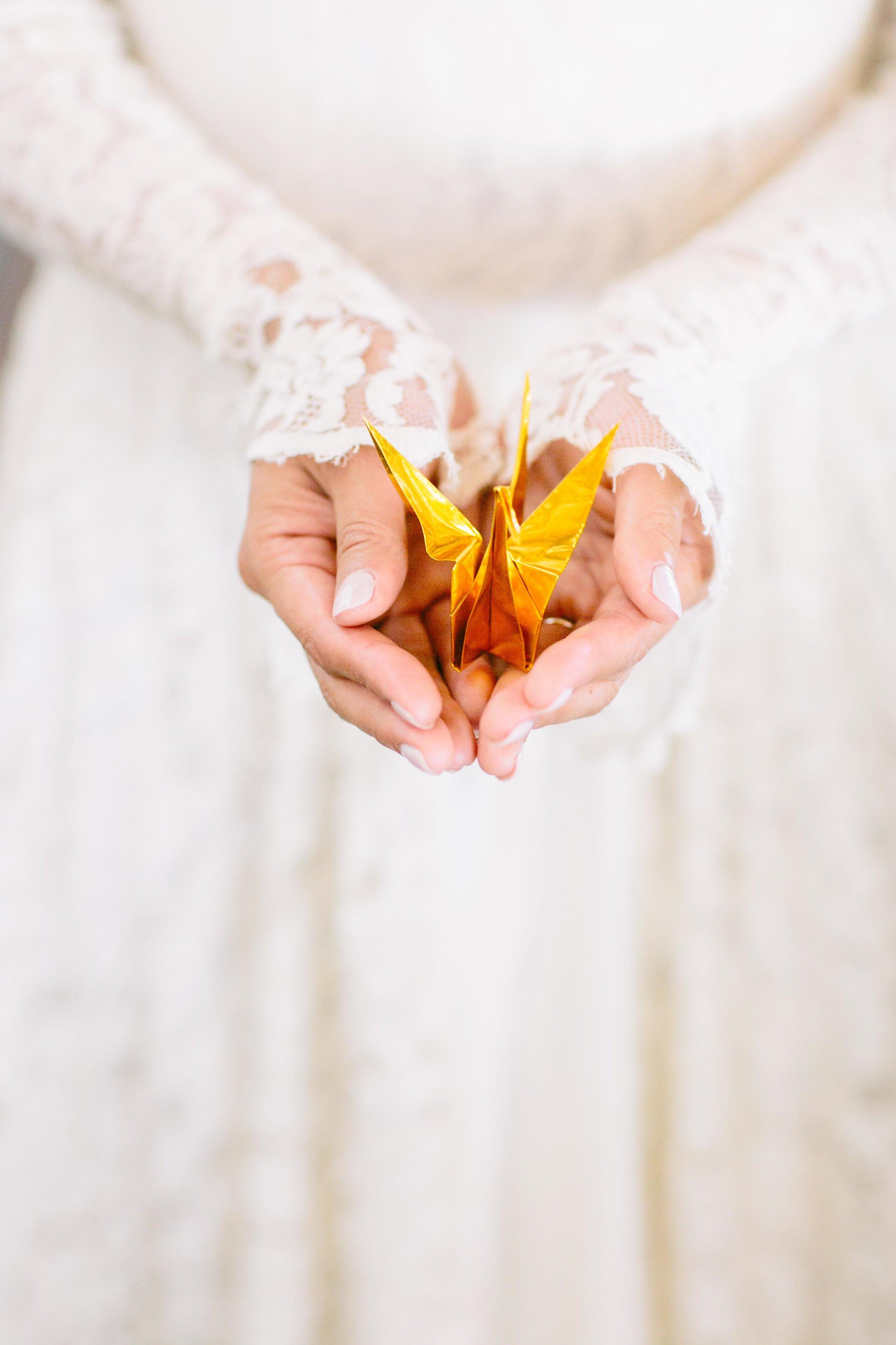 bride holding gold origami crane