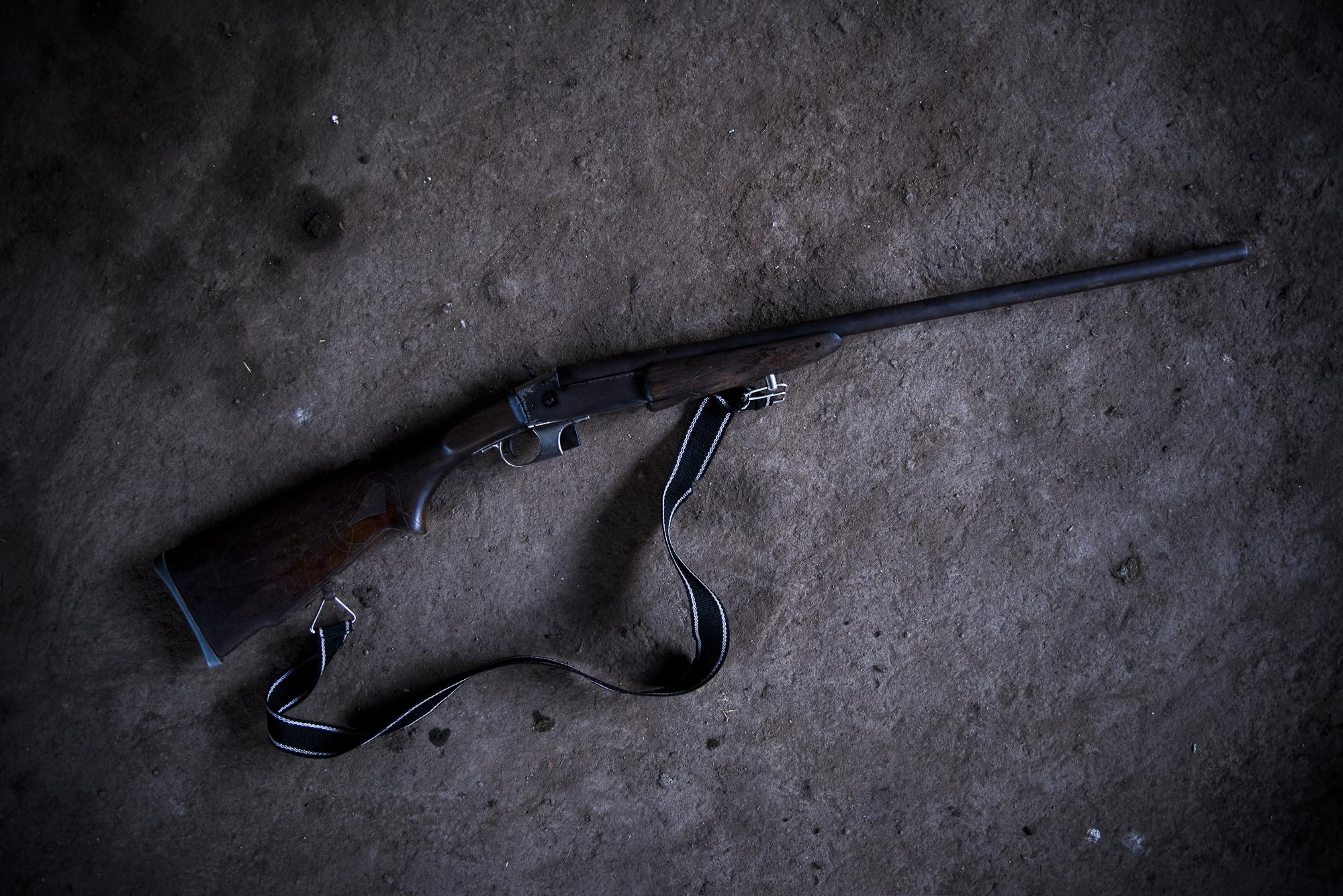 Catherine Perez no es capaz de empuñar un arma, sin embargo este rifle de caza adorna una esquina de su hogar. Solo lo usaria para ayuentar a los animales que intenten dañar su cultivo de platano con el que espera sacar a sus hijos adelante.