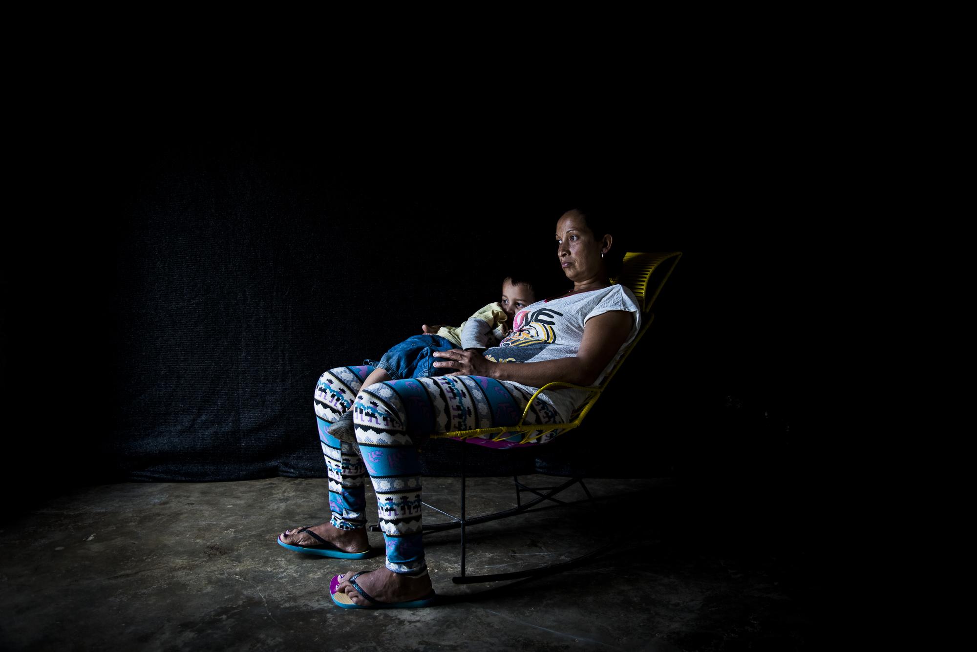 Gloria Areiza, vive en Sacramento, Magdalena. En 2001 cuando tenia 3 meses de embrazo y una niña de 6 meses de edad su esposo fue asesinado, su casa fue quemada y le toco huir. Aun vive con miedo, en una casa mitad cemento mitad tabla.