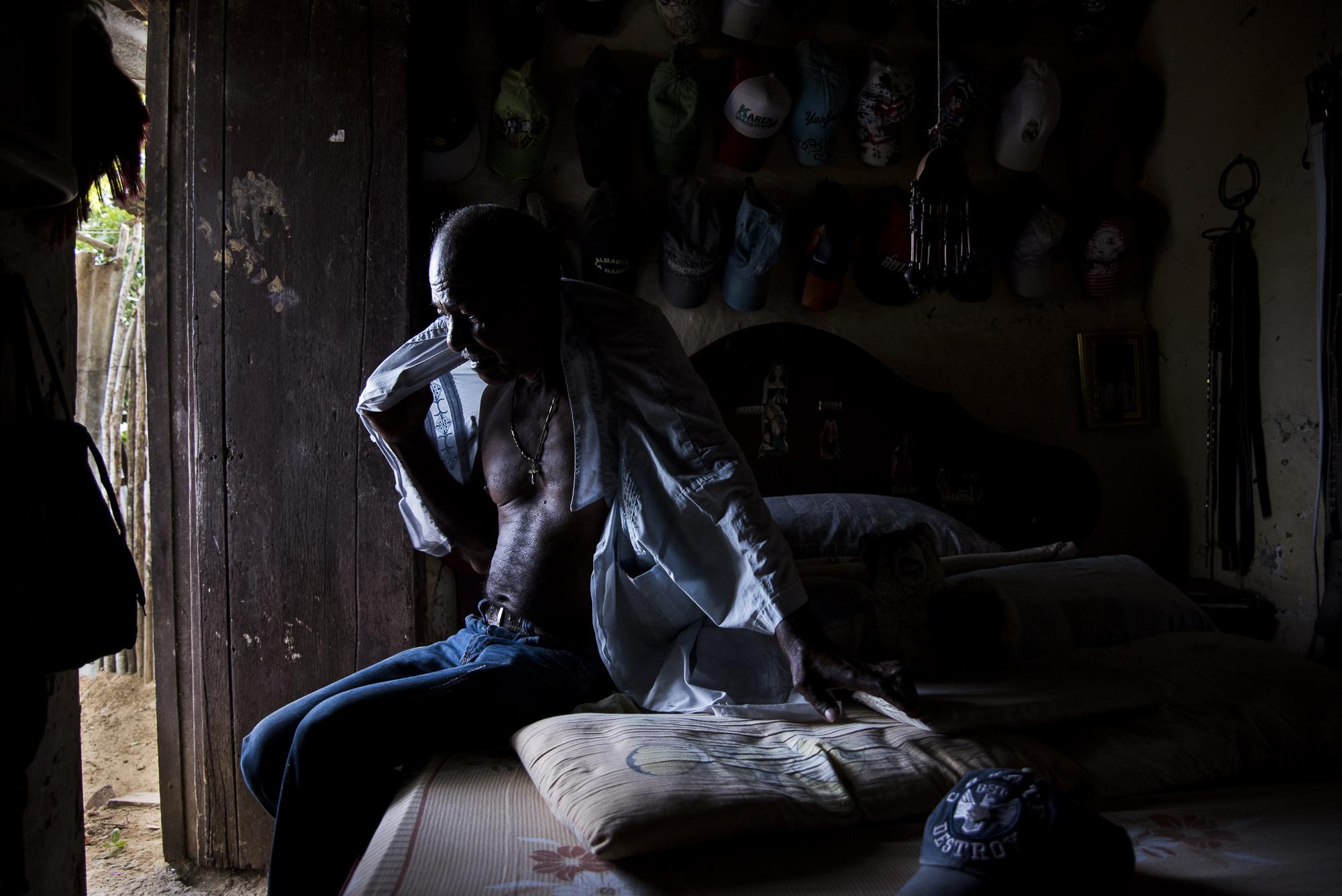 M. de 70 años se pone una camisa en la unica habitacion de su casa, ese lugar que para el no lo es por las condiciones en las que se encuentra El niega revelar su nombre por temor a represalias de grupos armados, para el, el miedo no se disipa con los años.